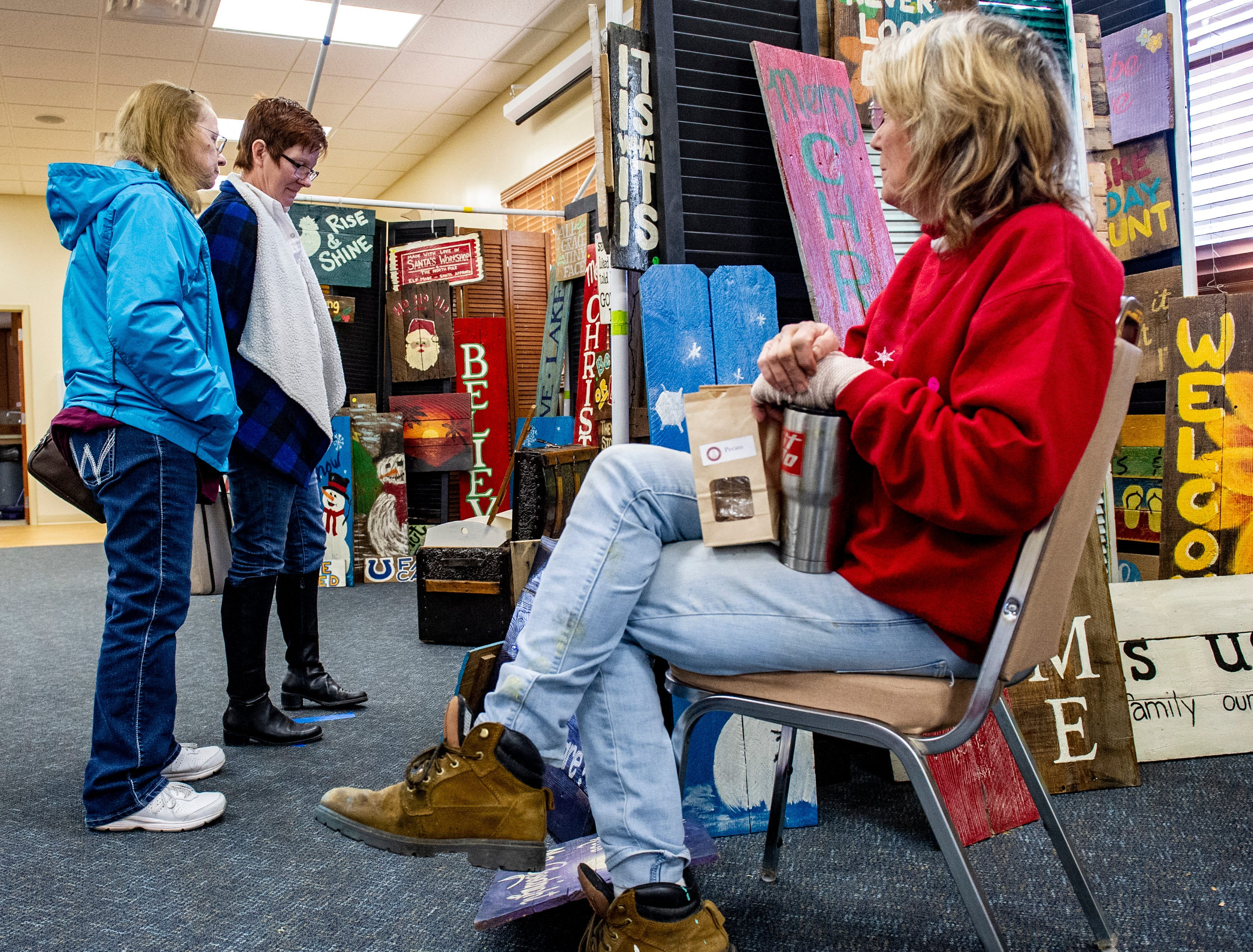 Deb Brown, left, and her friend Penny Greer shop the artist items offered by Joleen Kennedy, of Des Moines. Kennedy paints inspirational phrases on recycled wood. She said she took up the artwork after retiring to take care of her husband, a retired firefighter who has Alzheimer's disease. Kennedy's items were on display at the Rustiqueiowa Homespun Holiday Market held at the Trinity Presbyterian Church in Indianola Nov. 24, 2018.