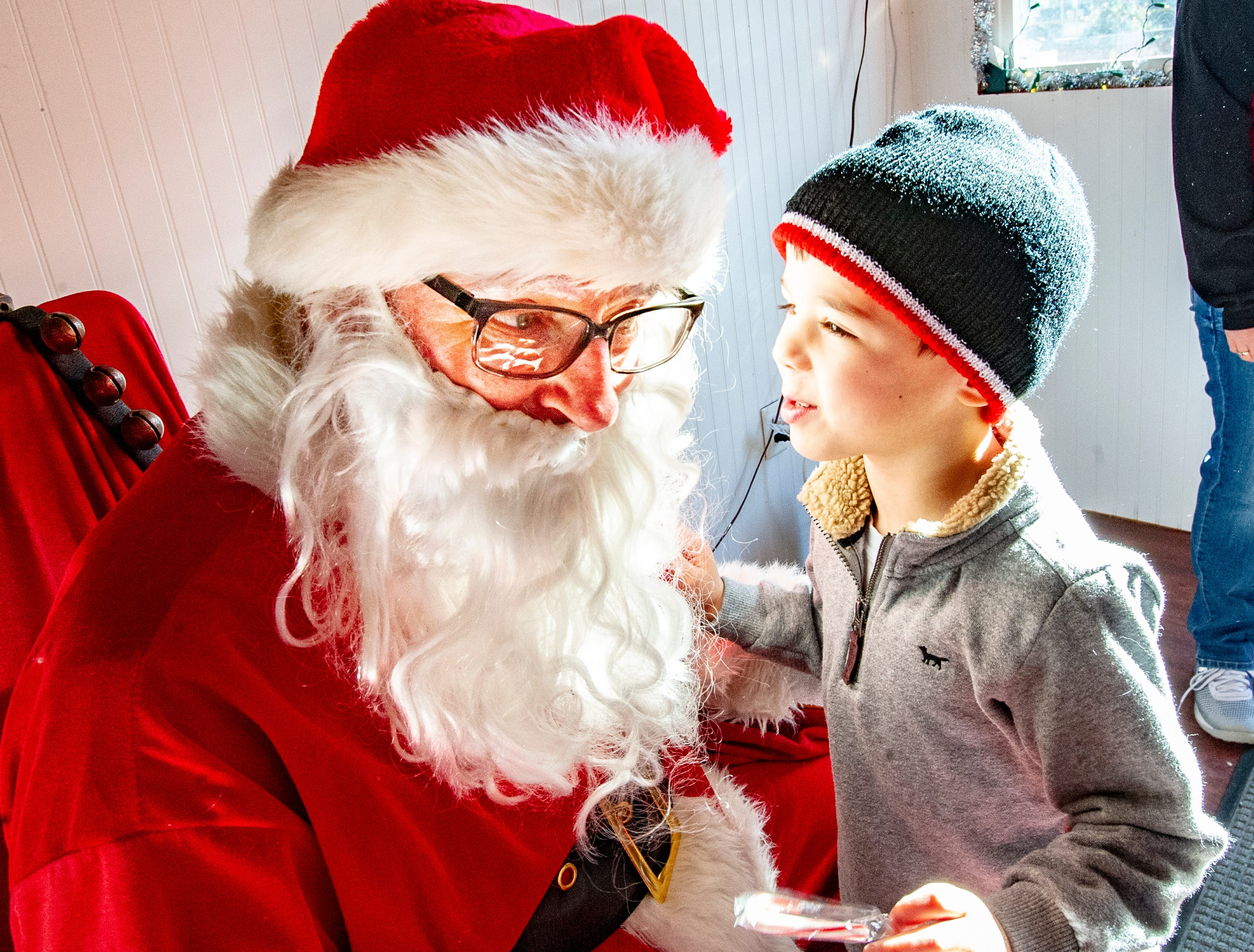 Jordan Ripley, 5, of Indianola whispers his Christmas wish list to Santa at the Santa House in downtown Indianola Nov. 24, 2018.