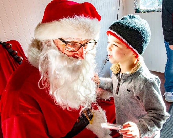 Jordan Ripley, 5, of Indianola whispers to Santa