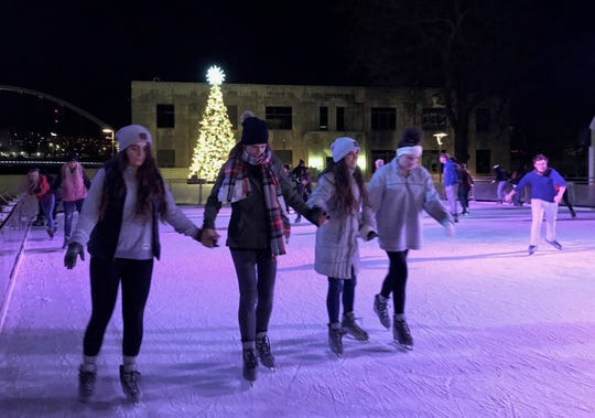 Friends enjoy ice skating at Brenton Skating Plaza in downtown Des Moines.