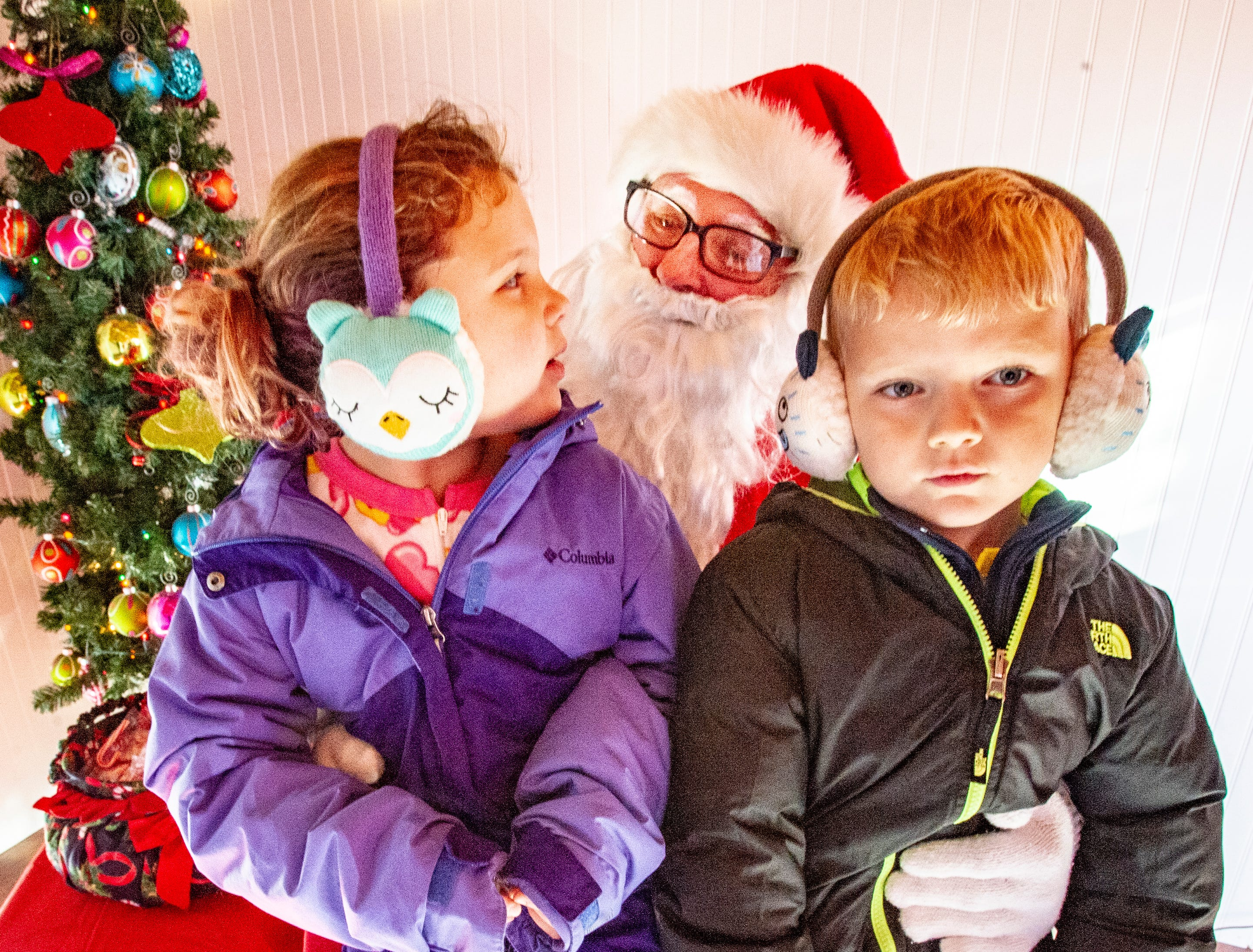 Jemma McAlexander, 8, and her brother Noah, 6, visit with Santa about the gift wish list. They are the children of Cortney and David McAlexander of Indianola. The two children met Santa at the Santa House in downtown Indianola Nov. 24, 2018.