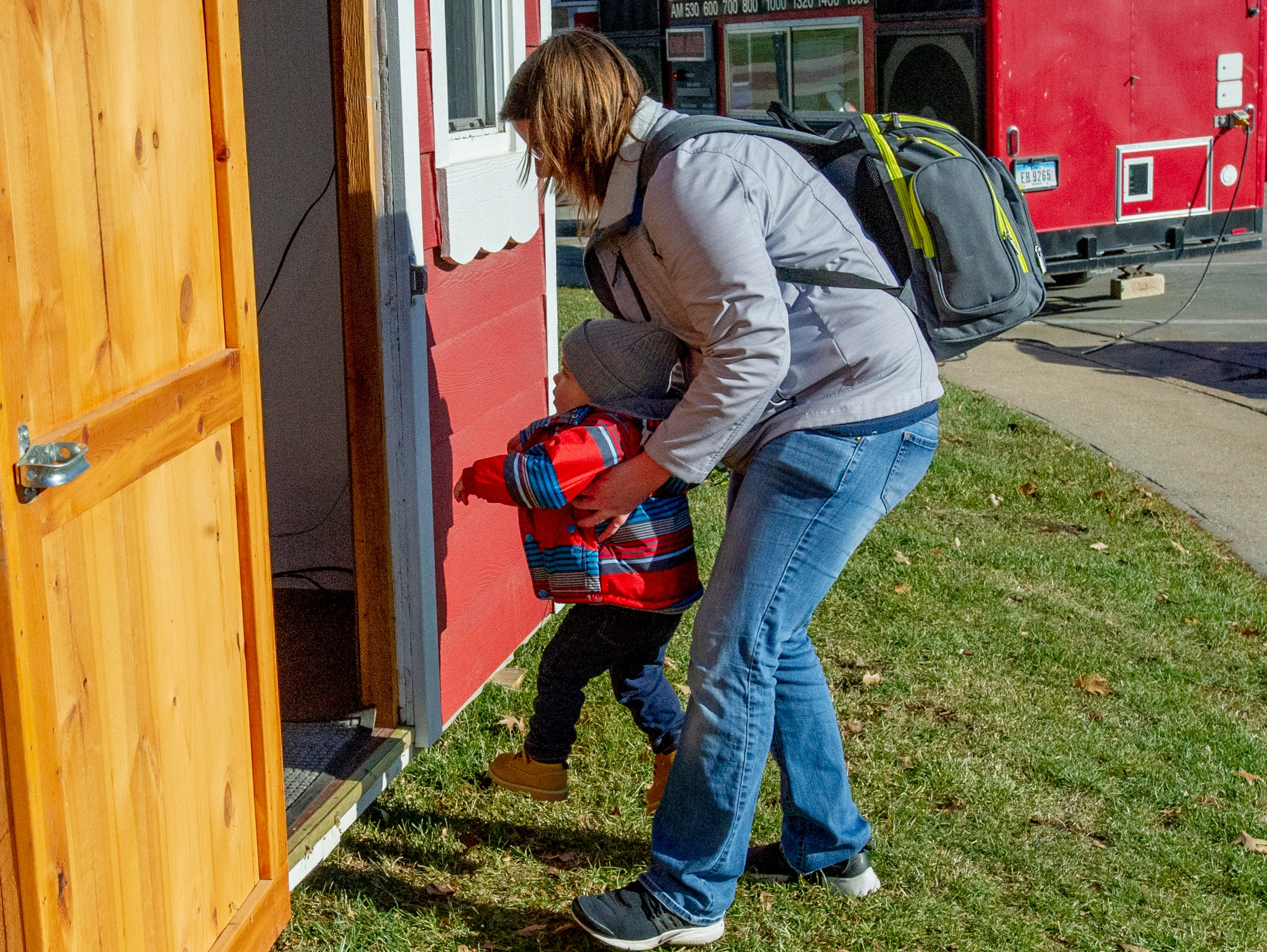 Amelia Leach helps her son Killian find the courage to visit Santa at the Santa House in downtown Indianola Nov. 24, 2018.