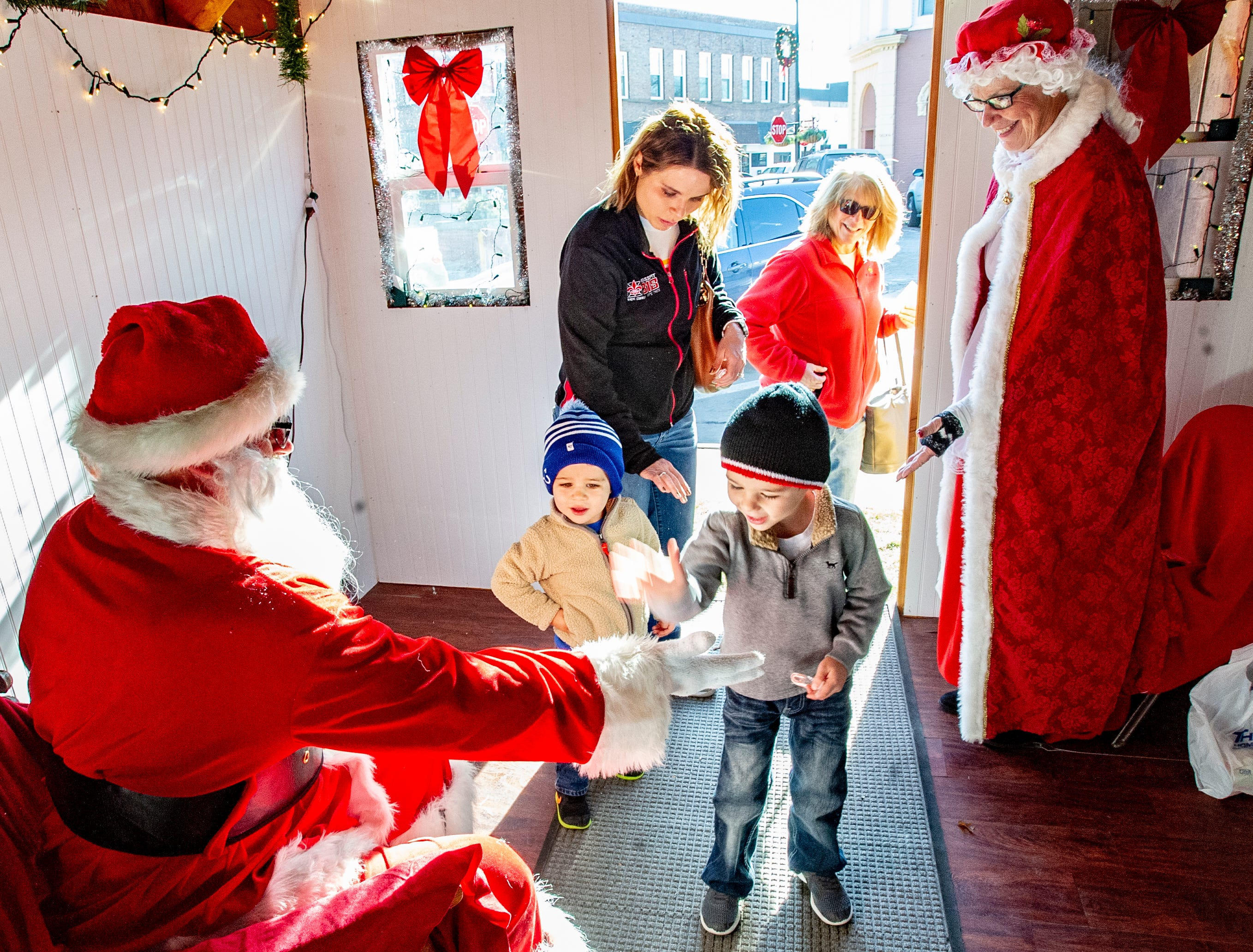 Ashley Ripley, of Indianola and her two boys, Simon, 2, and Jordan, 5, and the boys' grandmother, Julia Page of Osceola, visit with Santa and Mrs. Claus at the Santa House in downtown Indianola Nov. 24, 2018.