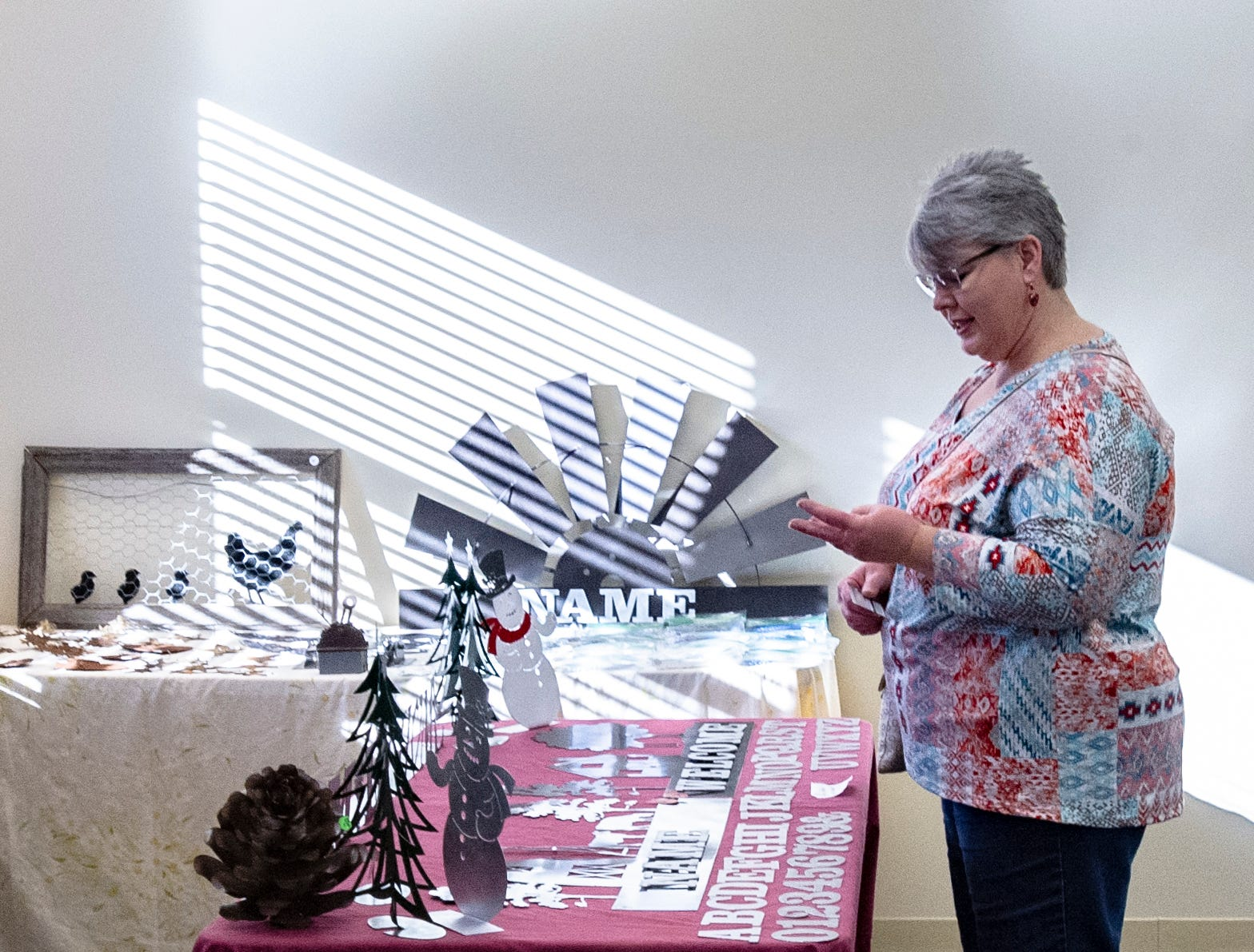 Donna Acheson, of Indianola, takes a look at the art made by  Pollock Welding of Mount Ayr at the Rustiqueiowa Homespun Holiday Market held at the Trinity Presbyterian Church in Indianola Nov. 24, 2018.