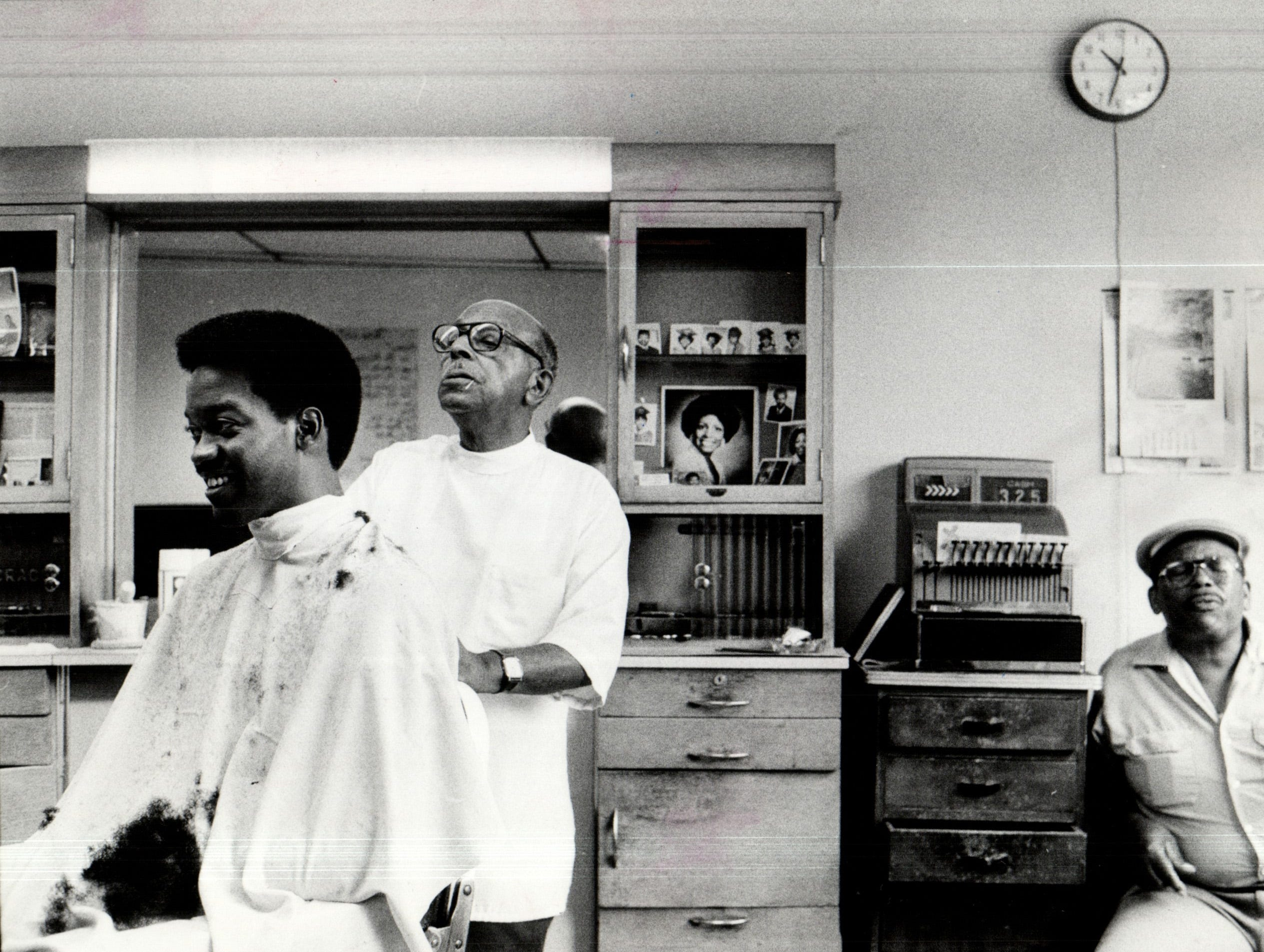 "Nokomis Talley gives Abraham Tearson a trim in the Artistic Barbershop on Chene in 1985. Talley said that before the Poletown neighborhood was cleared, ""There used to be people packed in here."""