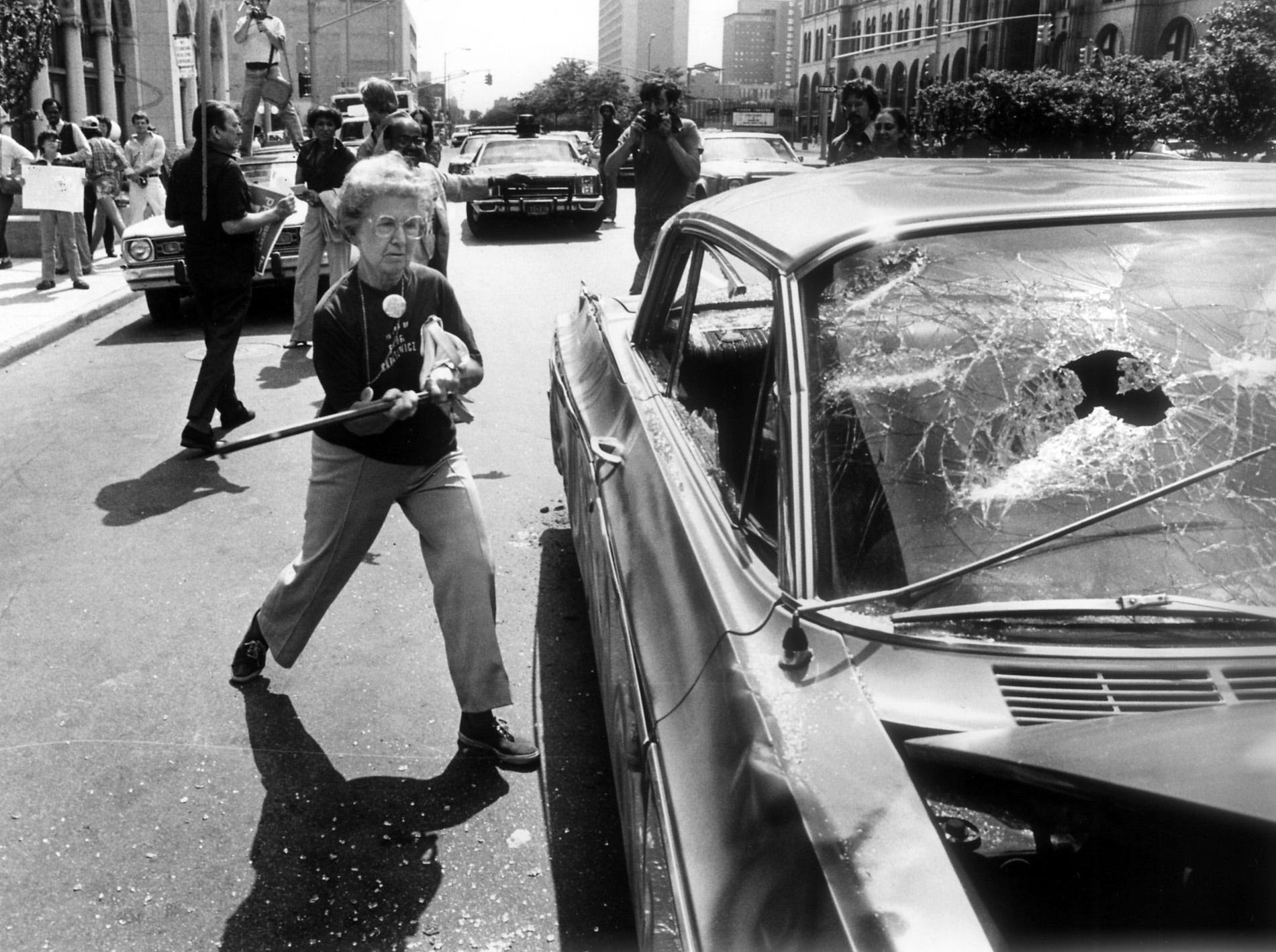 Marie Grucz, 71, takes out her frustration with General Motors on a faded gold 1964 Oldsmobile as about 40 protesters assembled in front of the GM headquarters in the Detroit's New Center area. The city of Detroit forced out 3,438 residents and demolished 1,300 homes.
