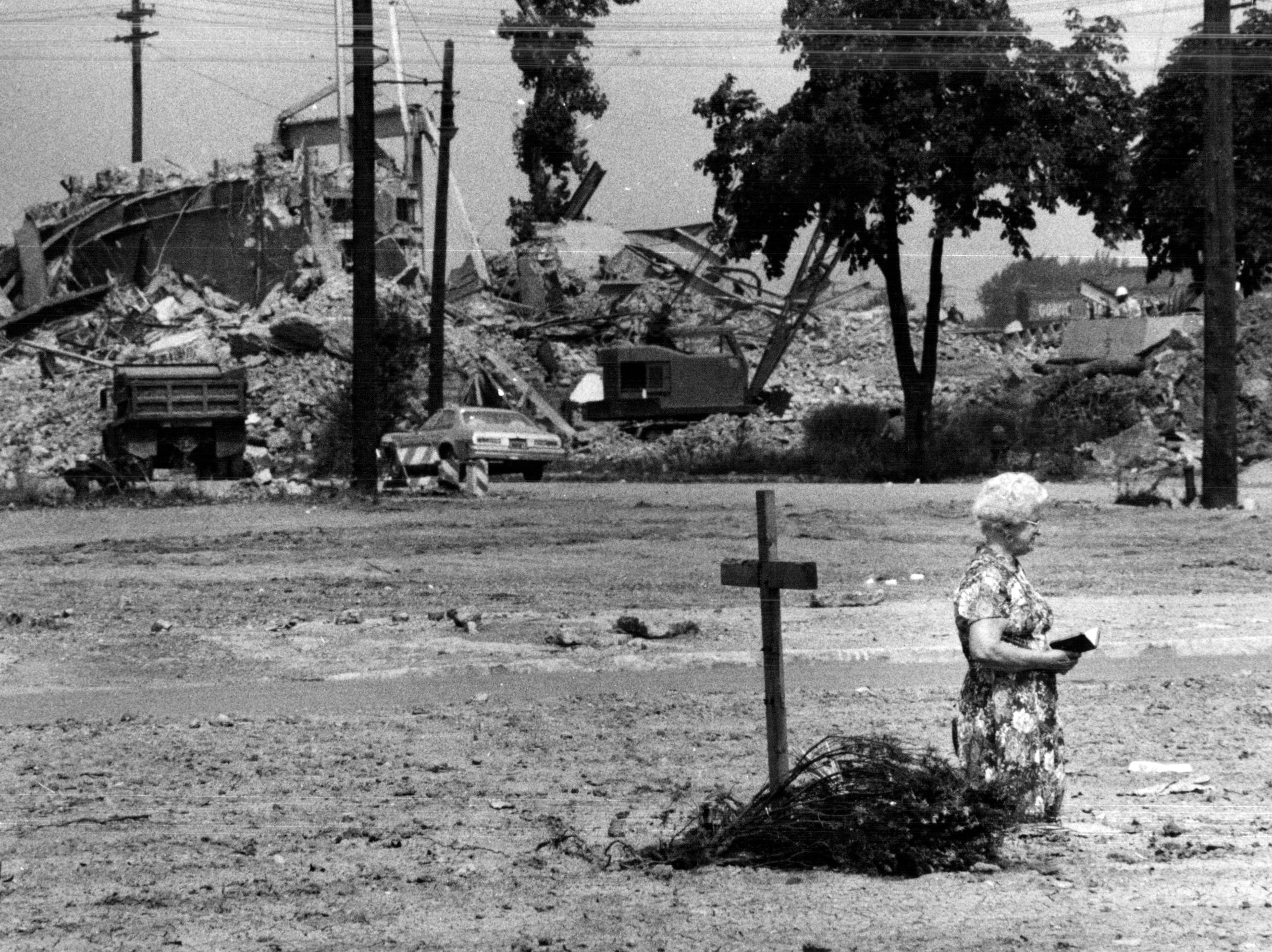 Josephine Jakubowski prays at the leveled site of her church, the Immaculate Conception Church, in Detroit, Michigan's Poletown neighborhood. She and many others had protested the demolition but General Motors and the city of Detroit leveled a neighborhood to build a factory.