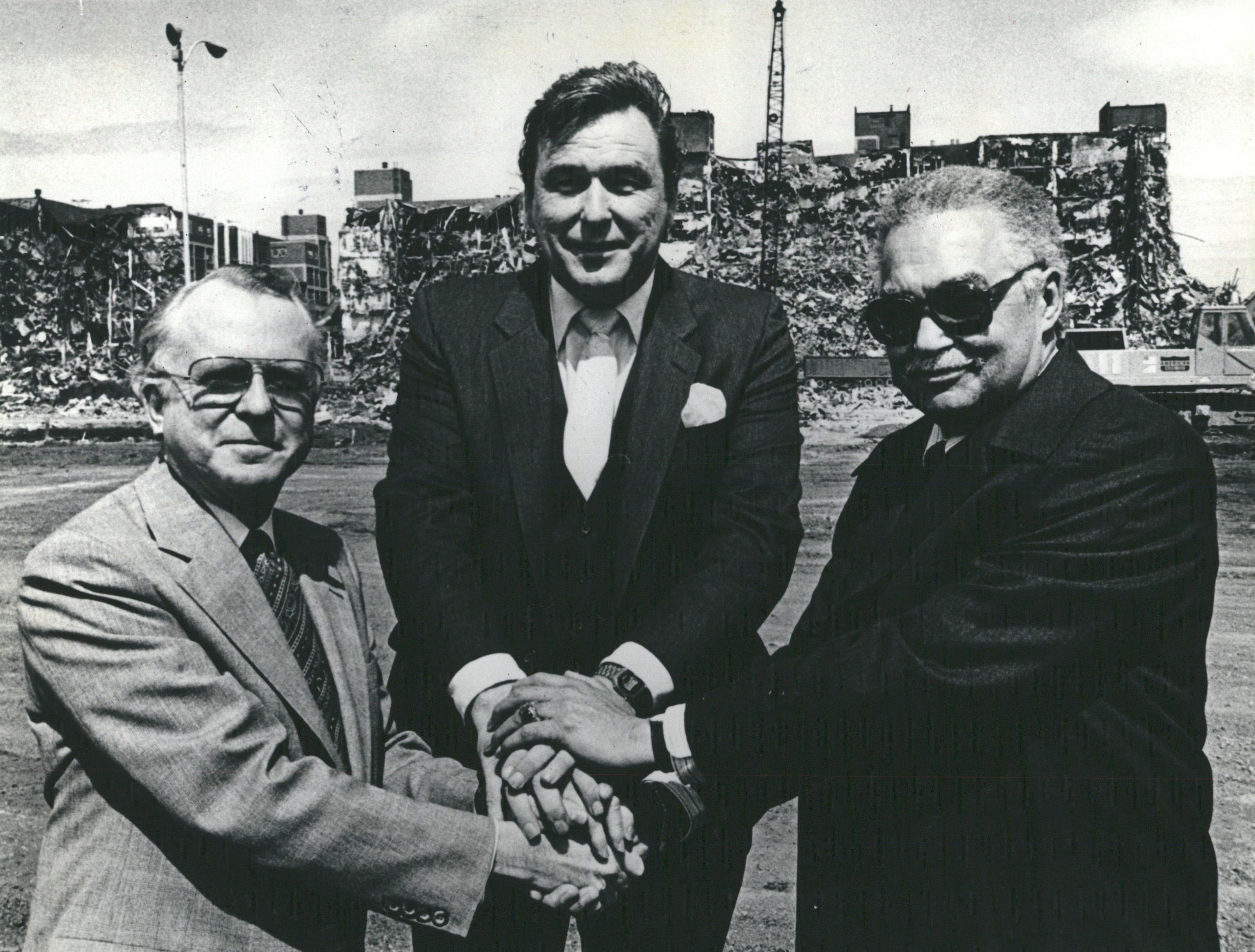 In May 1981, Mayor Young shakes hand with General Motors Chairman Roger Smith, on left, and Hamtramck Mayor Robert Kozaren at groundbreaking ceremonies for GM's Poletown project. Behind them is the wreckage of Dodge Main.
