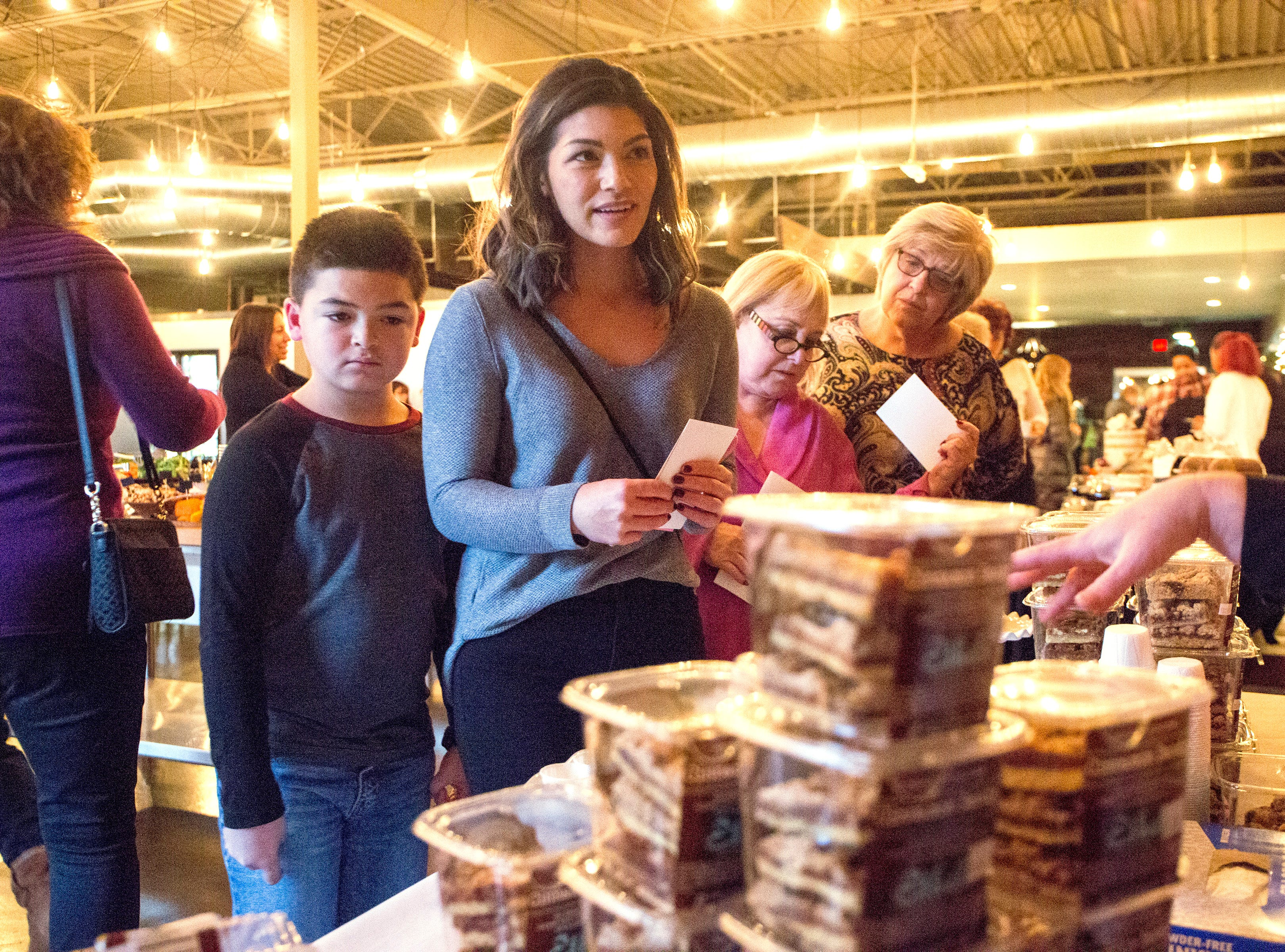 From left, Manny Velazquez, 8 and Aerin Velazquez, 34 of Sterling Heights sample baked goods at the Ethel's Baking Co. display during the Whisked event at the Great Lakes Culinary Center in Southfield, Mich., Sunday, Nov. 18, 2018.