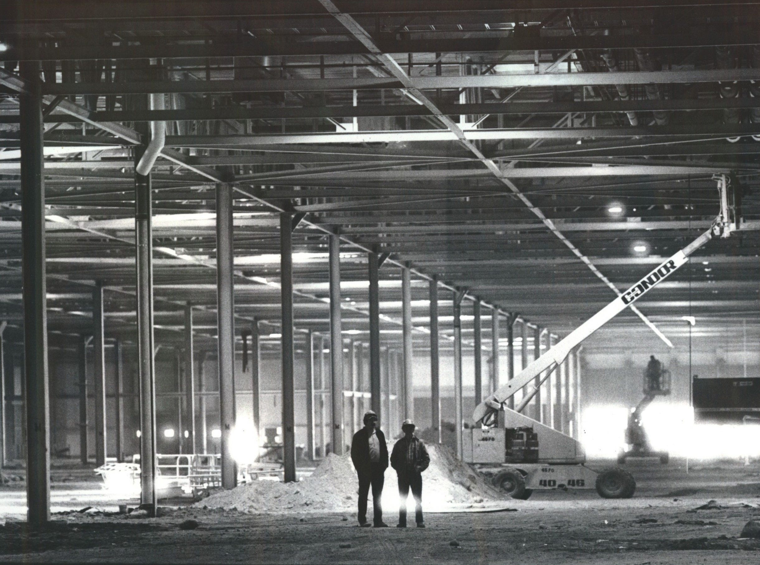 Two unidentified workers stand amid construction of the GM Poletown assembly plant.