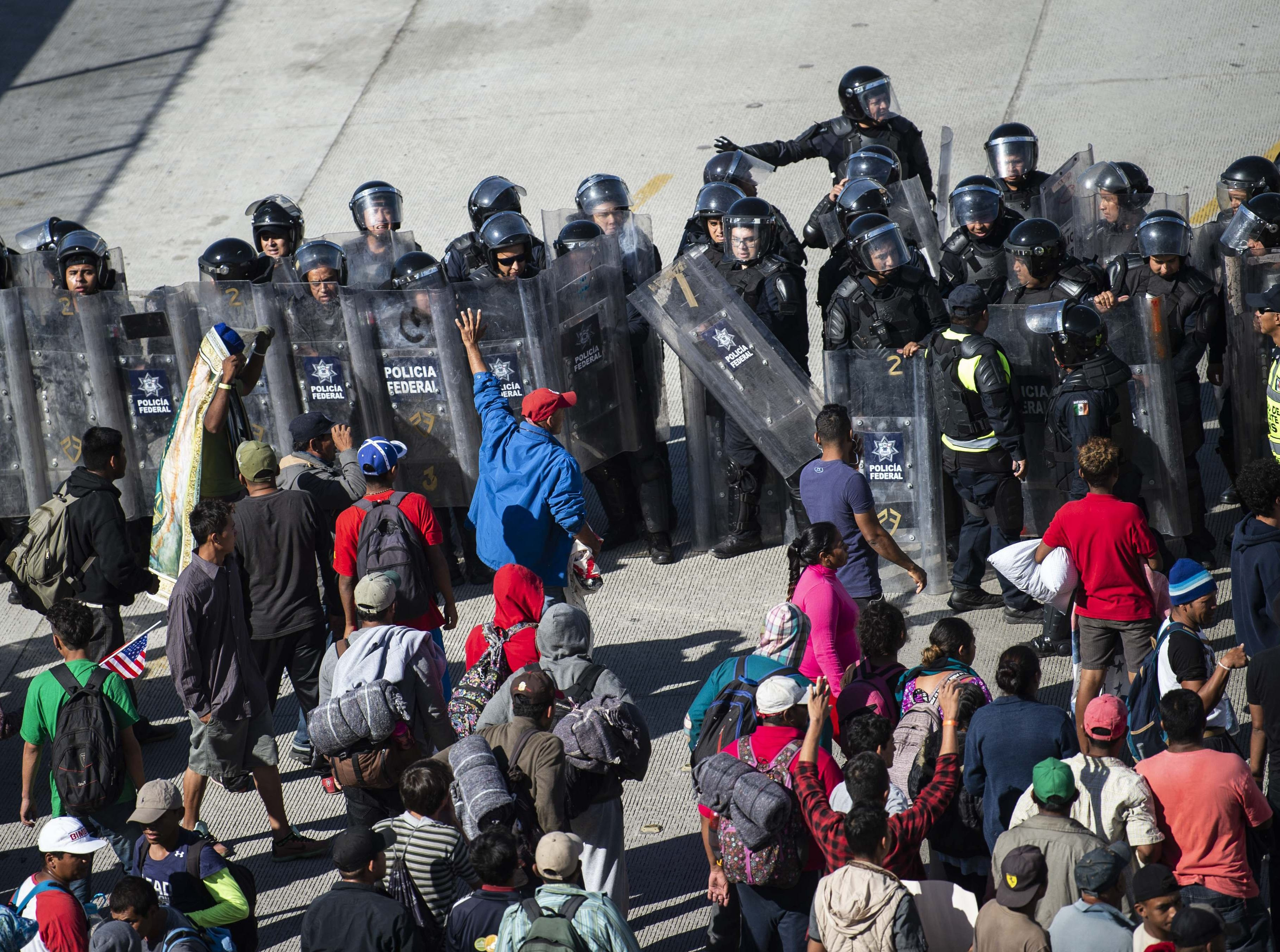 Central American migrants -- mostly Hondurans -- are blocked by Mexican police as they reach the El Chaparral border crossing, in Tijuana, Baja California State, Mexico, on November 25, 2018. - Hundreds of migrants attempted to storm a border fence separating Mexico from the U.S. on Sunday amid mounting fears they will be kept in Mexico while their applications for asylum are processed. An AFP photographer said the migrants broke away from a peaceful march at a border bridge and tried to climb over a metal border barrier in the attempt to enter the United States.