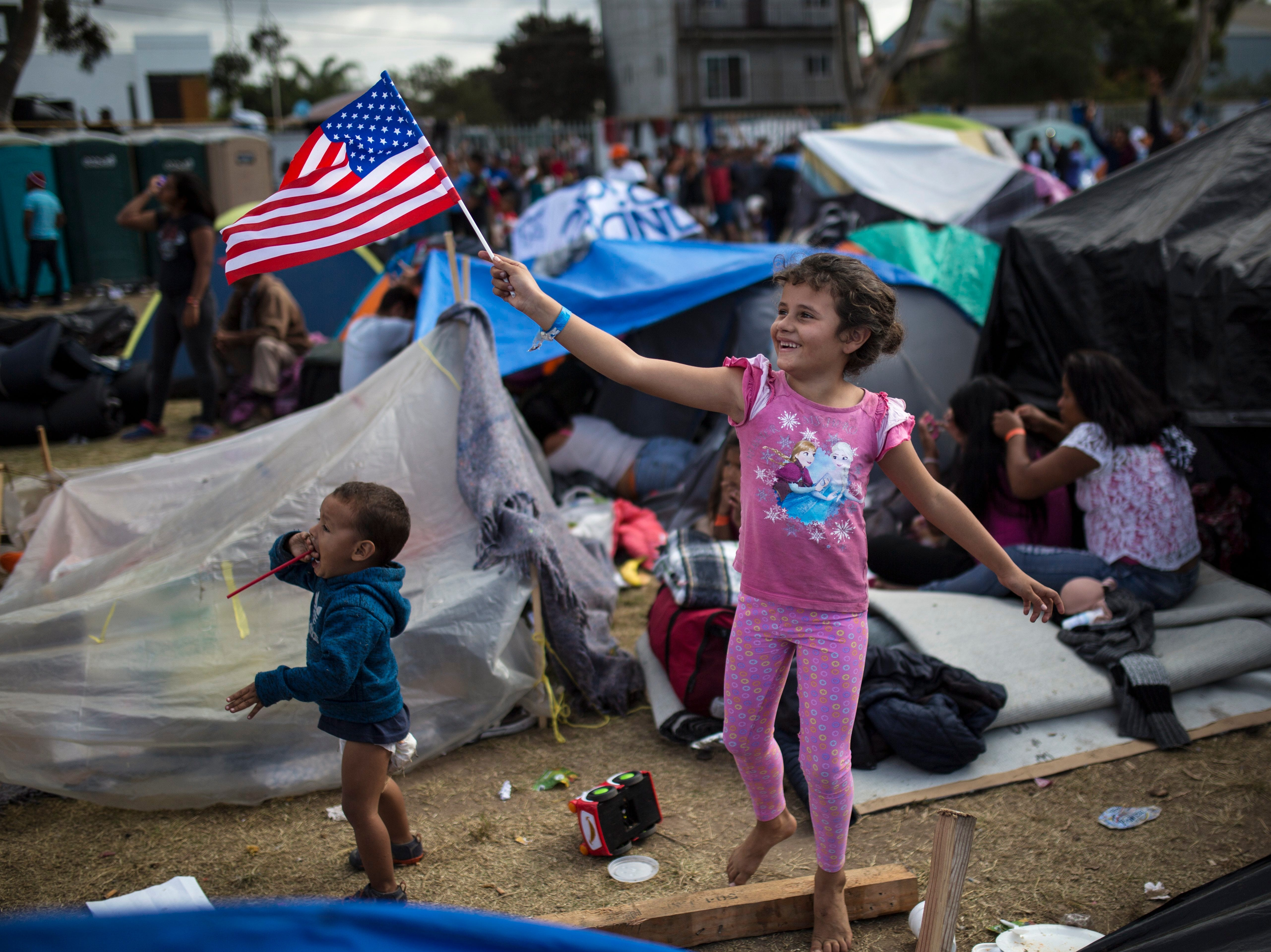 Seven-year-old Honduran migrant Genesis Belen Mejia Flores waves an American flag at U.S. border control helicopters flying overhead near the Benito Juarez Sports Center, which is serving as a temporary shelter for migrants, in Tijuana, Mexico, Saturday, Nov. 24, 2018.
