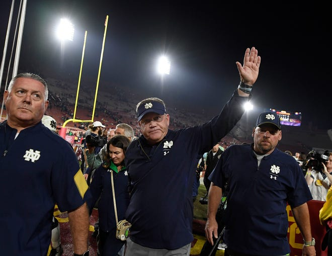Head coach Brian Kelly of the Notre Dame Fighting Irish waves as he walks off the field Saturday at Los Angeles Memorial Coliseum after defeating the USC Trojans.