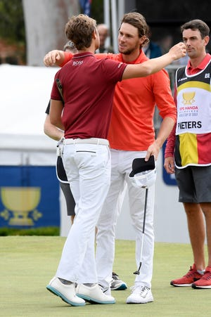 Belgium's Thomas Detry, left, and Thomas Pieters hug each other on the 18th green after winning the World Cup of Golf.