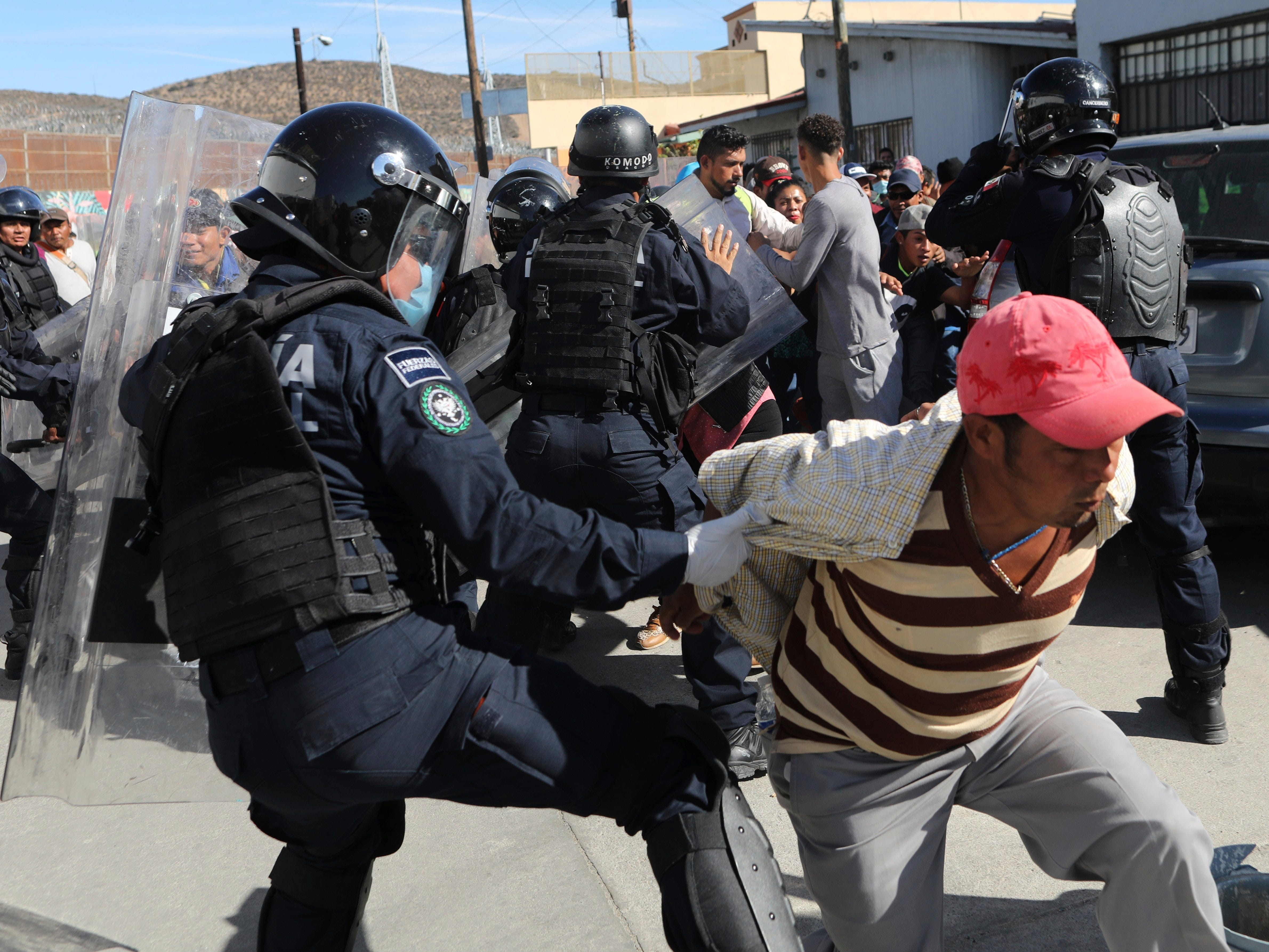 Migrants try to push past Mexican police on the Mexico-U.S. border at the Chaparral crossing in Tijuana, Mexico, Sunday, Nov. 25, 2018, as they try to reach the U.S. The mayor of Tijuana has declared a humanitarian crisis in his border city and says that he has asked the United Nations for aid to deal with the approximately 5,000 Central American migrants who have arrived in the city.