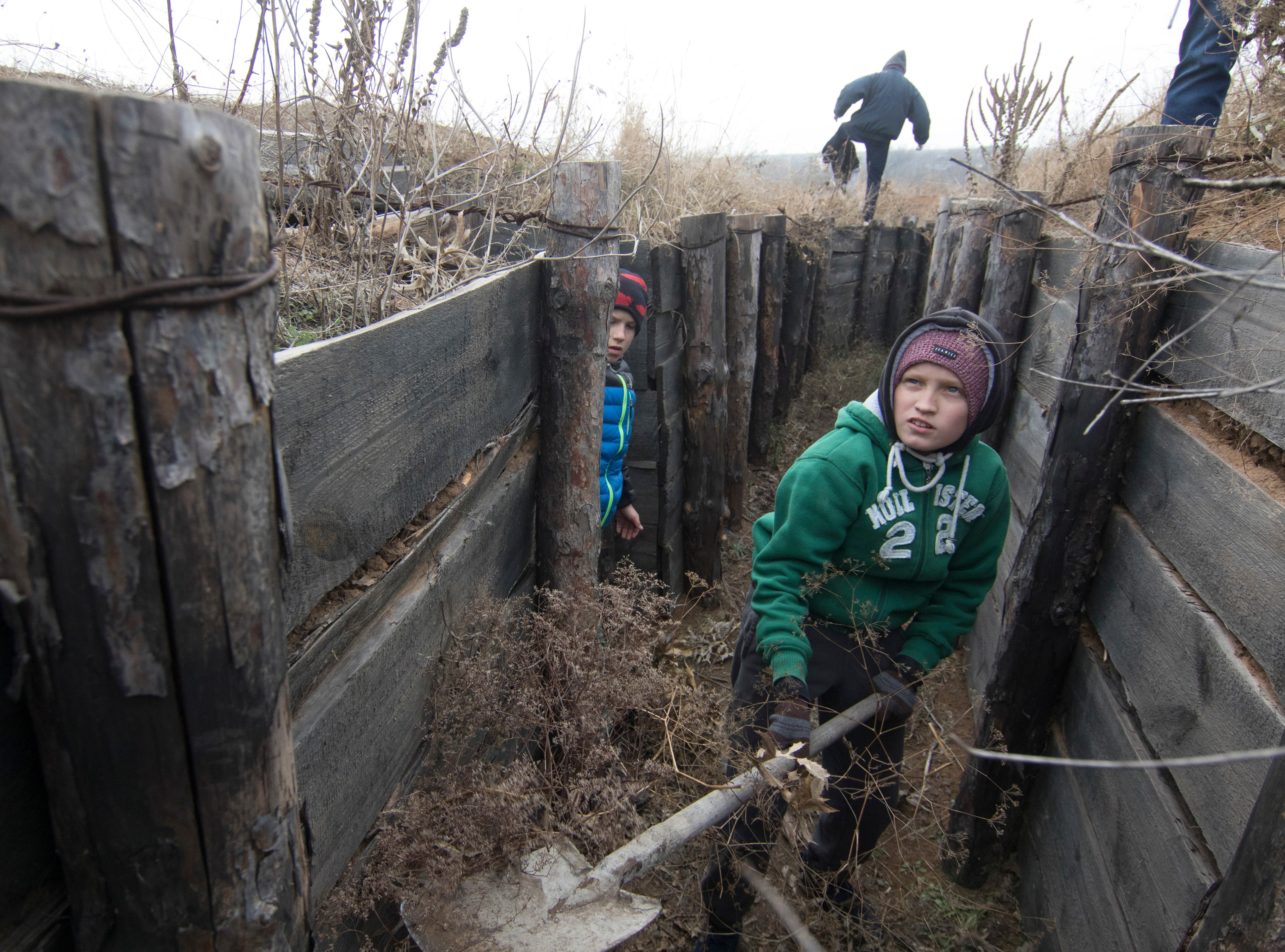 Children from an orphanage volunteer to help strengthen trenches on Ukraine's Army positions near Rybatske, Ukraine, Monday, Nov. 26, 2018.