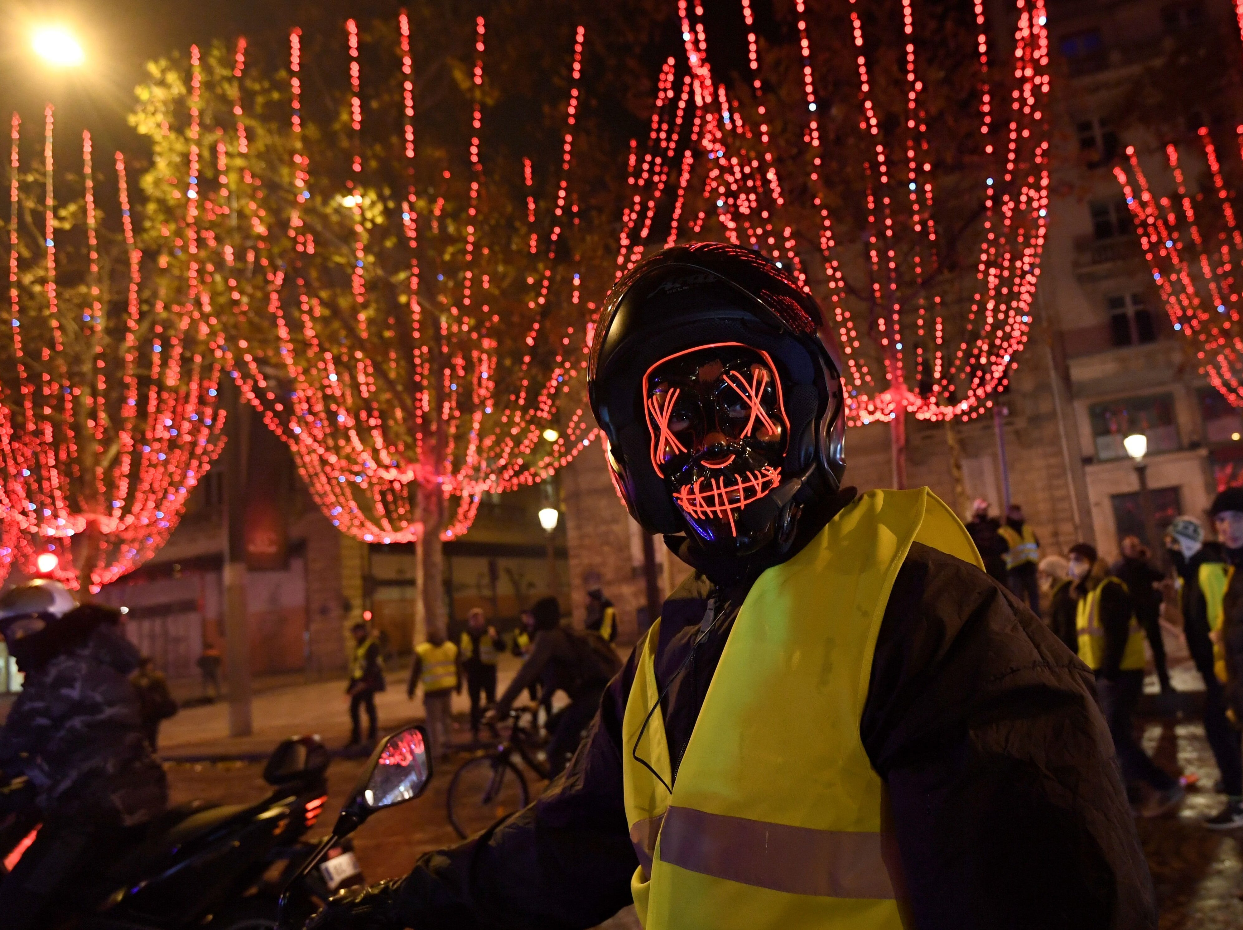 A masked protester poses on a scooter near The Arc de Triomphe on the Champs Elysees in Paris, on November 24, 2018, during a rally against rising oil prices and living costs.