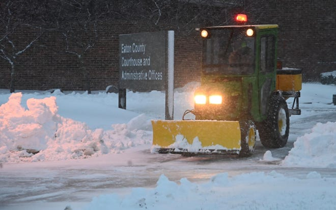 Eaton county workers clear mounds of snow from the entrance to the courthouse in Charlotte where former MSU president Lou Anna Simon is scheduled to be arraigned today, November 25.