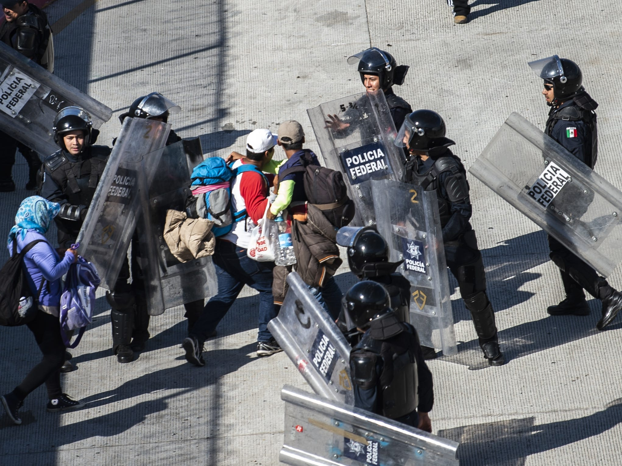 Central American migrants struggle with Mexican police forces as they reach the El Chaparral border crossing, in Tijuana, Baja California State, Mexico, on November 25, 2018.