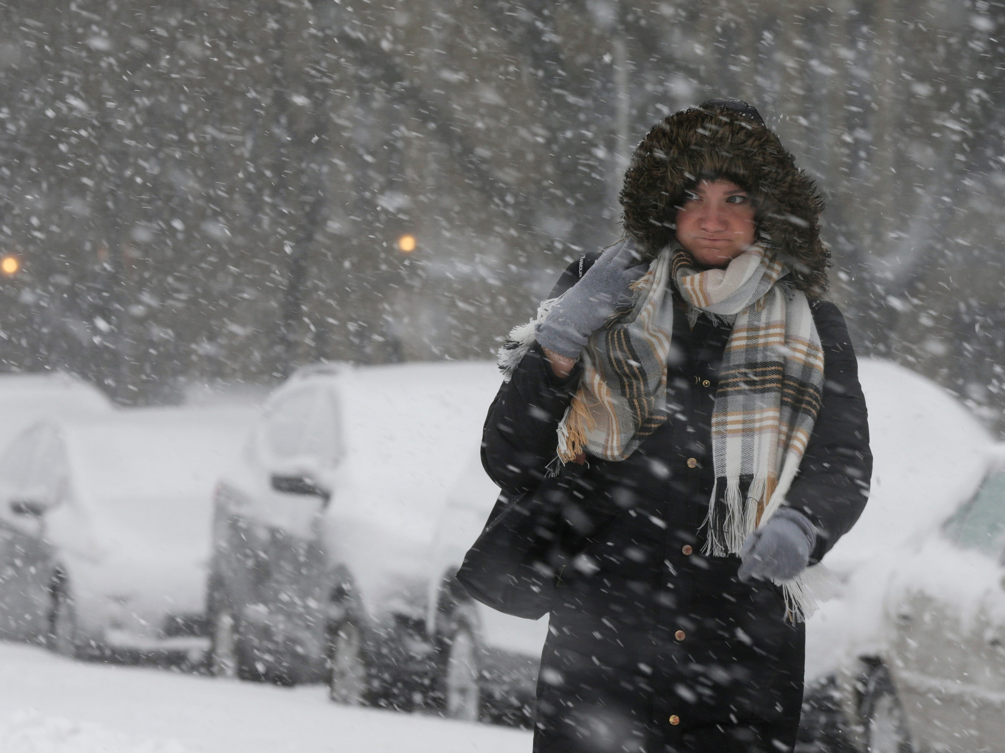 A commuter walks to a bus stop as snow falls, Monday, Nov. 26, 2018, in Chicago. A wintry storm brought blizzard-like conditions to parts of the Midwest early Monday, grounding hundreds of flights and causing some road traffic chaos as commuters returned to work after the Thanksgiving weekend.