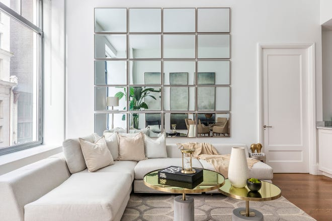 A wall of mirrors helps a small living room feel open and spacious. (Design Recipes)