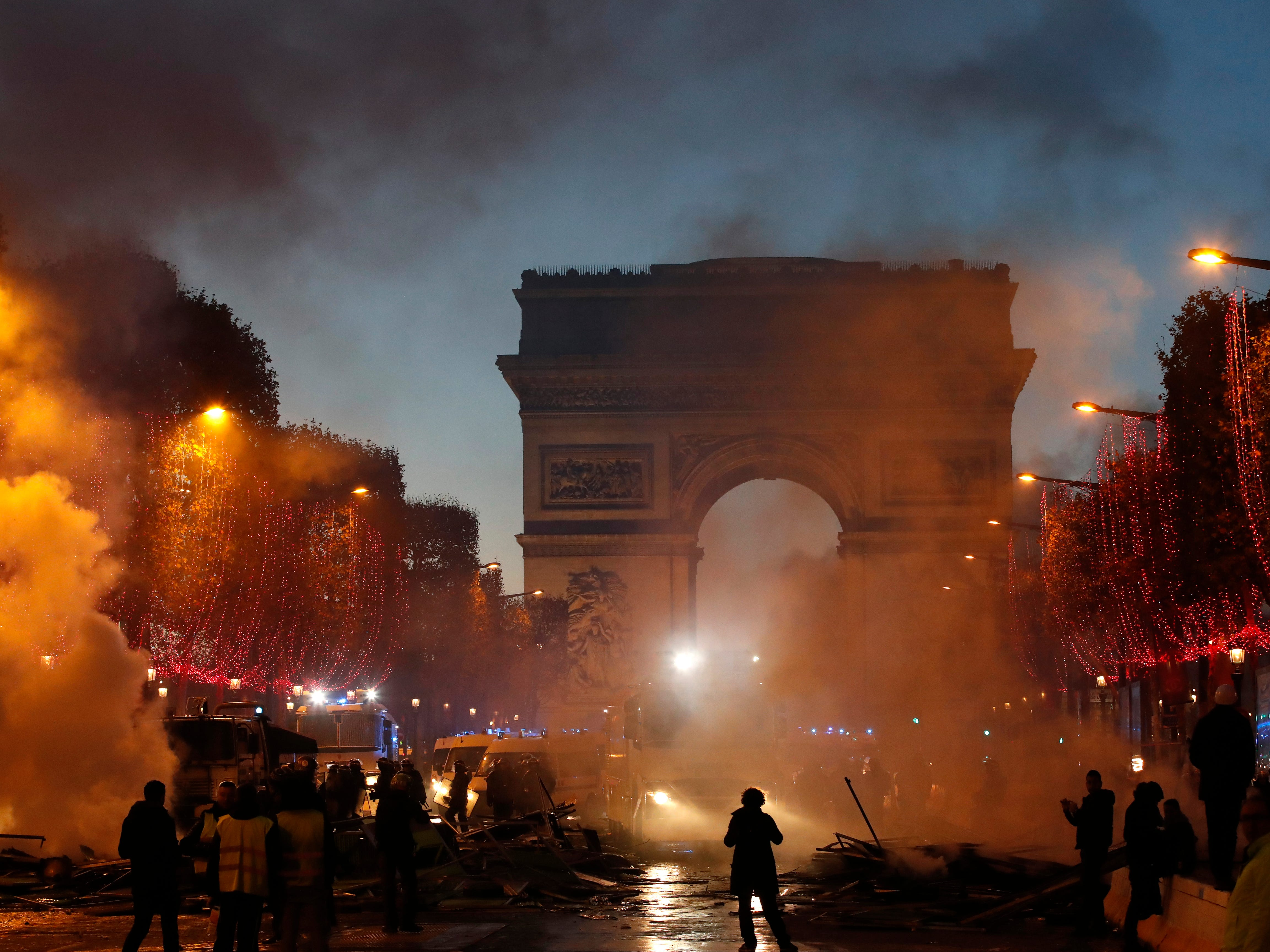 Plumes of smoke are seen near the Arc de Triomphe on the Champs-Elysees avenue decorated with the Christmas lightings during a protest against fuel taxes Saturday, Nov. 24, 2018, in Paris.