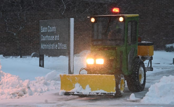 Eaton county workers clear mounds of snow from the entrance to the courthouse in Charlotte where former MSU president Luana K Simon is scheduled to be arraigned today, Nov. 25, 2018.
