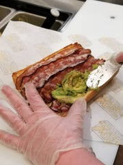 Freshly cut avocado is added to a toasted BLT in the making at Which Wich.