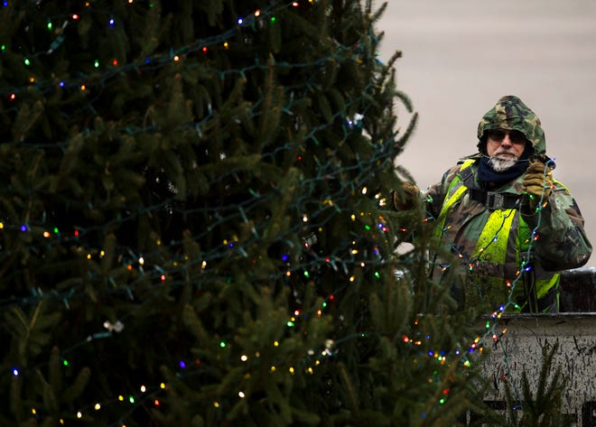 Mike Forcum, an electrician with the City of Evansville Traffic Engineering Department, strings lights around the 28-foot-tall Norway spruce outside the Civic Center Monday afternoon. The City of Evansville's annual Christmas Tree lighting ceremony will take place Wednesday night at 5 p.m. and the Reitz Memorial High School Choir will perform. The tree was donated by Richard Sanford and will have about 250,000 LED lights.