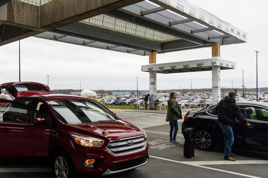People load their bags into cars underneath a covered walkway that is almost finished being built at Evansville Regional Airport, Monday afternoon, Nov. 26, 2018. The airport's $20 million renovations that were started about a year ago are nearly complete.