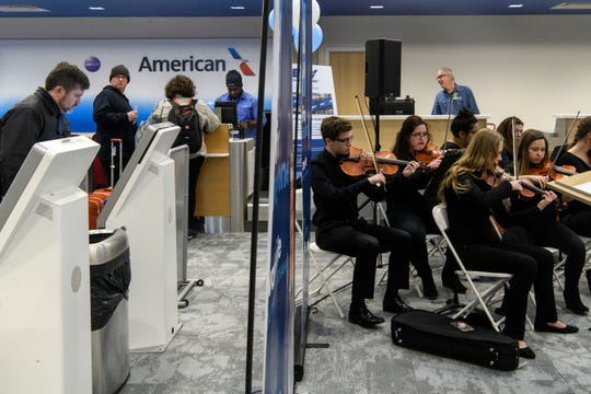 Travelers check in for their flight with American Airlines as North High School orchestra students play music for the press conference held to showcase the Evansville Regional Airport's nearly completed $20 million renovations, Monday afternoon, Nov. 26, 2018.