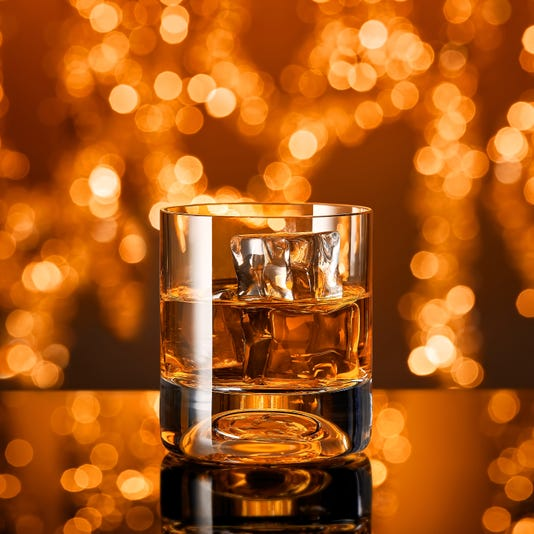 Glass Of Whiskey With Ice Cubes In Front Of Christmas Lights
