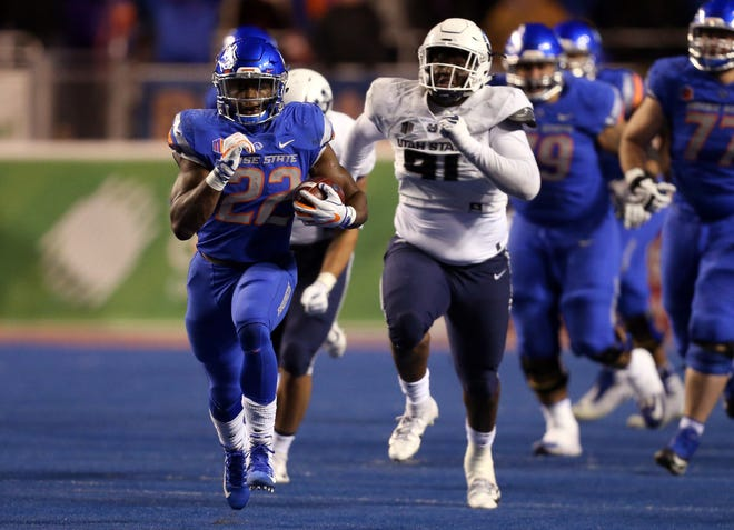 Boise State running back Alexander Mattison runs away from Utah State's defense during the Broncos' 33-24 win over the Aggies on Saturday night at Albertsons Stadium in Boise, Idaho. Mattison fan for 200 yards and three touchdowns to help Boise State secure a spot in the Mountain West championship game for the third time in six years.