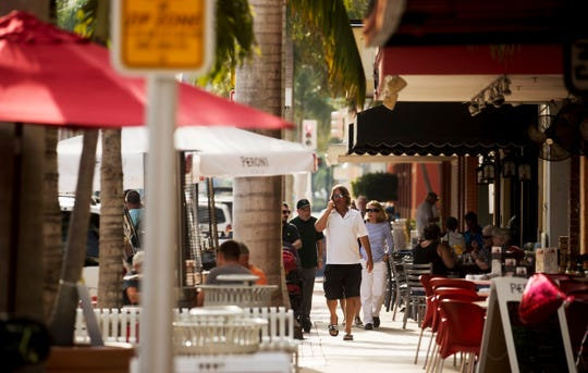 Pedestrians enjoy an afternoon in downtown Fort Myers on Monday 11/26/2018. Temperatures have hovered in the 80's recently but are fixing to plummet as a cold front heads this way.