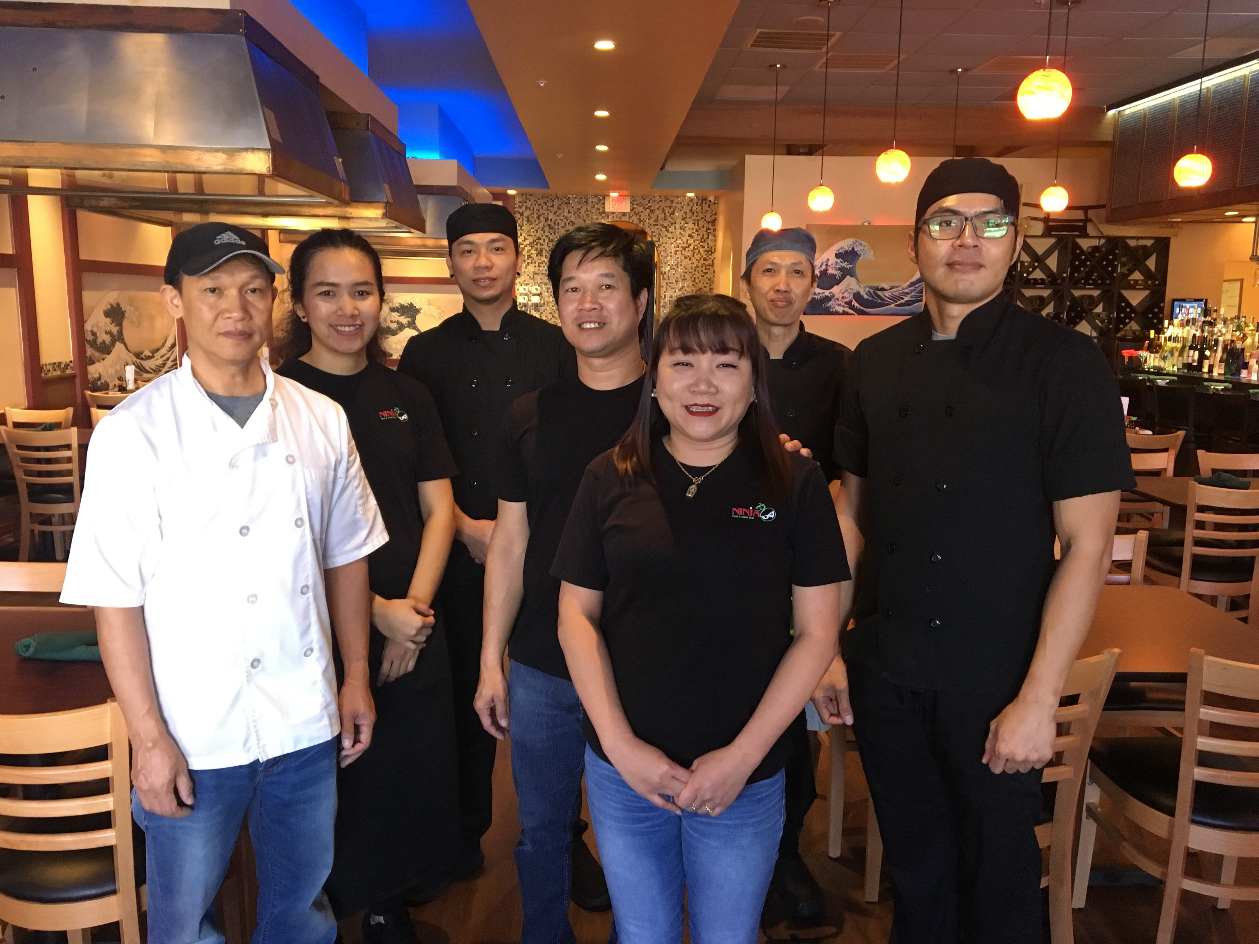 """Pop Thienthongkham  and Ni Komenjumrust with the staff of their restaurant, Ninja Thai & Sushi in south Fort Myers. """"This is our big dream,"""" Komenjumrust said."""