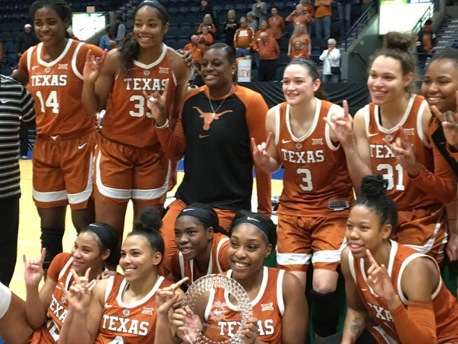 """Texas women gives the """"Hook 'Em Horns"""" sign after topping Fordham for Gulf Coast Showcase women's hoop title on Sunday at Hertz Arena."""