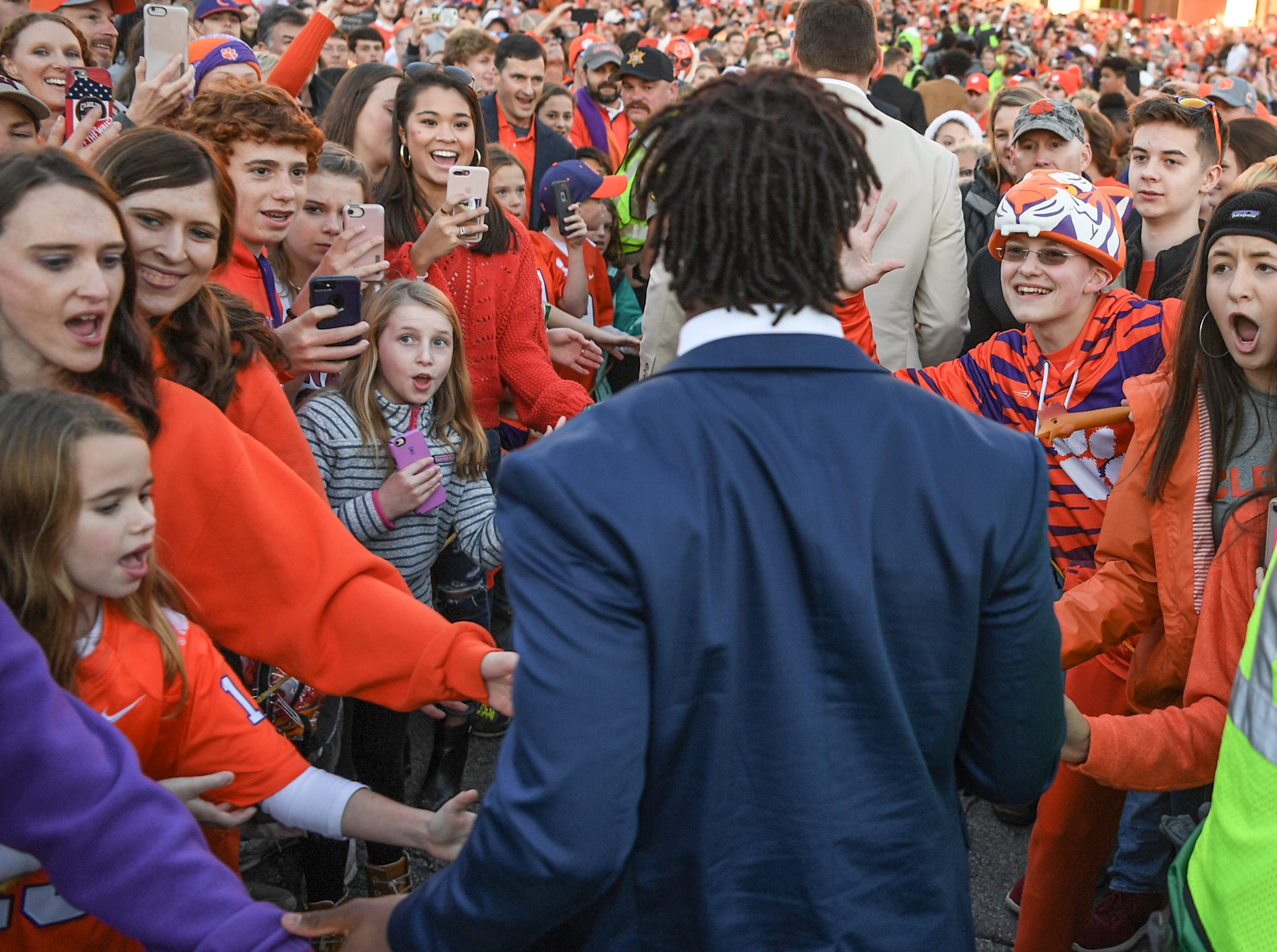 Clemson running back Travis Etienne walks by fans during Clemson Tiger Walk before kickoff outside Memorial Stadium, before the South Carolina at Clemson football game in Clemson on Saturday, November 24, 2018.
