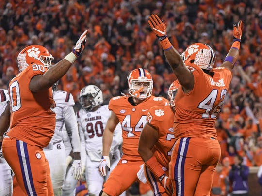 Clemson defensive lineman Christian Wilkins, right, celebrates with defensive lineman Dexter Lawrence (90) and tight end Garrett Williams (44), middle, after leaping over South Carolina linebacker Sherrod Greene(44) for a touchdown during the second quarter in Memorial Stadium on Saturday, November 24, 2018.