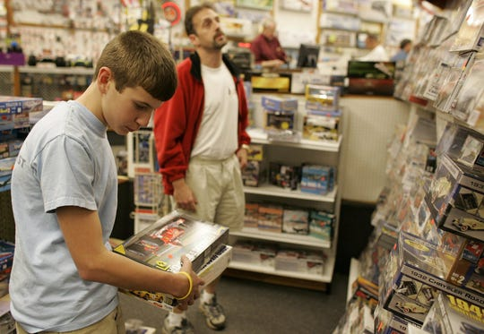 Mark Boudoucies and his son, Derek, 12, shop for holiday gifts at The Great Escape in Greenville on Nov. 24, 2004.