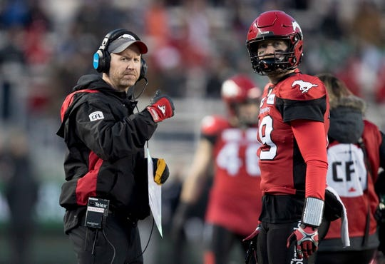 Calgary Stampeders coach Dave Dickenson speaks with quarterback Bo Levi Mitchell during the first half against the Ottawa Redblacks during the Canadian Football League Grey Cup in Edmonton, Alberta, on Sunday.
