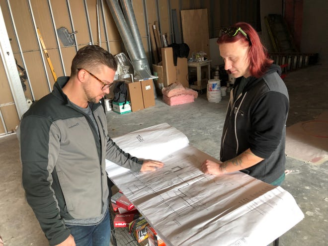Tappers owners Austin Howard, left, and Jeff Moulton, right, look at blueprints for the arcade bar's expansion into the space next door.