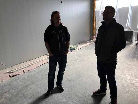Tappers owners Jeff Moulton, left and Austin Howard, right, stand in the soon-to-be expansion site for the arcade bar.