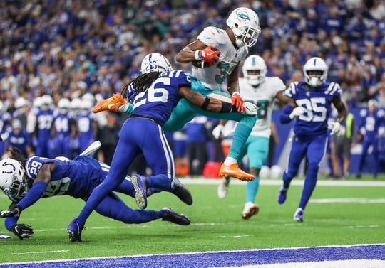 Miami Dolphins running back Kenyan Drake (32) jumps over Indianapolis Colts free safety Malik Hooker (29), landing in the end zone for touchdown during the second half of the game at Lucas Oil Stadium in Indianapolis, Sunday, Nov. 25, 2018. The Colts won, 27-24.