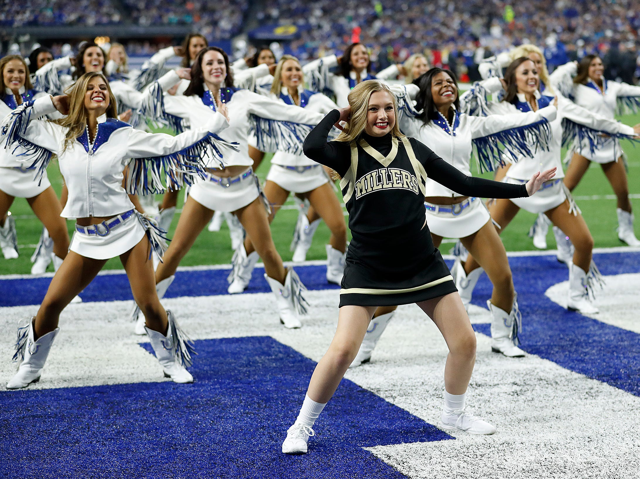 Ella Whisler, Noblesville West Middle Schooler, dances with the Indianapolis Colts cheerleaders in the first half of their game at Lucas Oil Stadium on Sunday, Nov. 25, 2018.