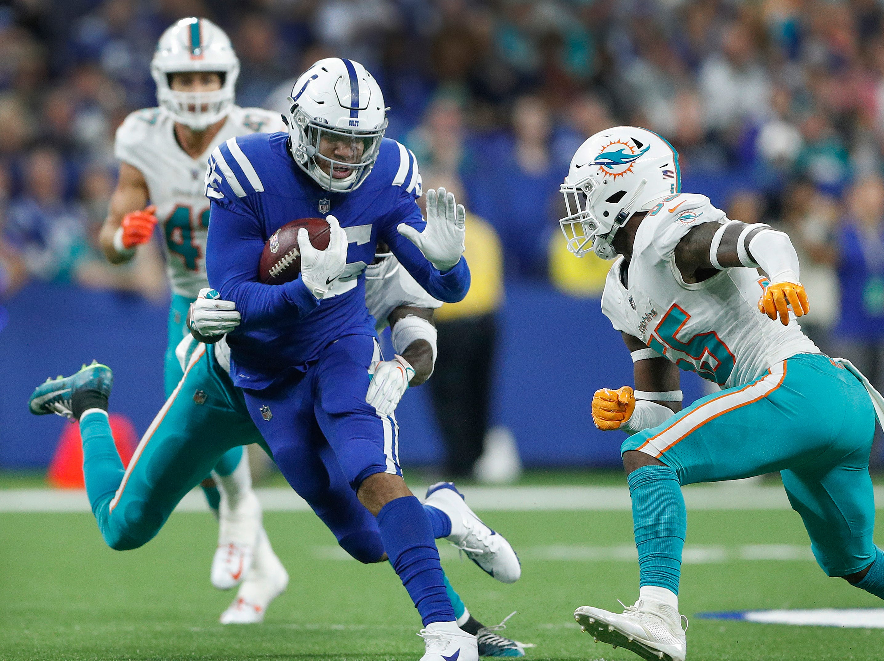 Indianapolis Colts tight end Eric Ebron (85) braces for the hit by Miami Dolphins outside linebacker Jerome Baker (55) in the second half of their game at Lucas Oil Stadium on Sunday, Nov. 25, 2018. The Colts defeated the Dolphins 27-24.