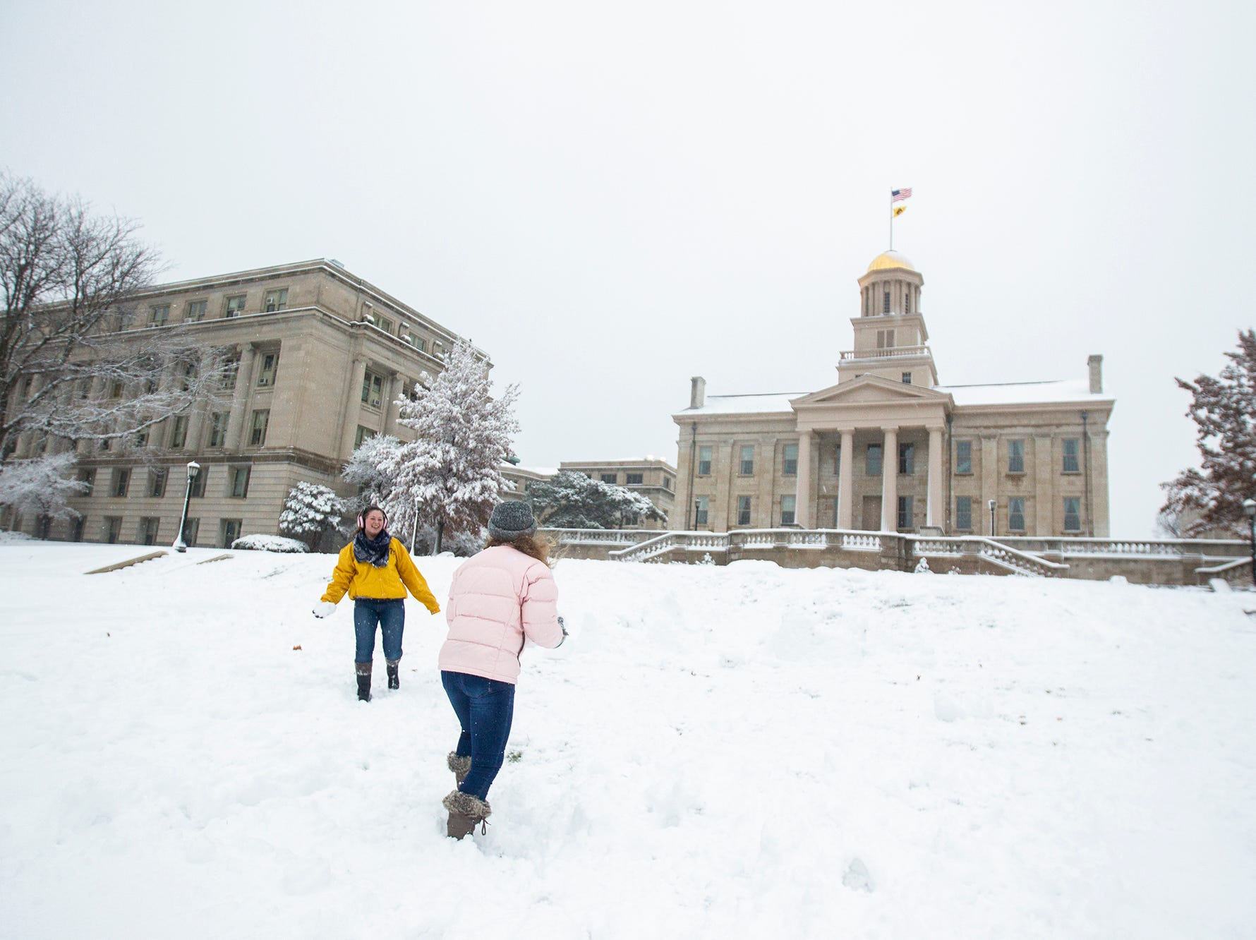 University of Iowa freshman Sarah Nighswonger, left, and Caroline Pickart throw snowballs during a snow storm on Sunday, Nov. 25, 2018, on the west side of the Pentacrest in Iowa City.