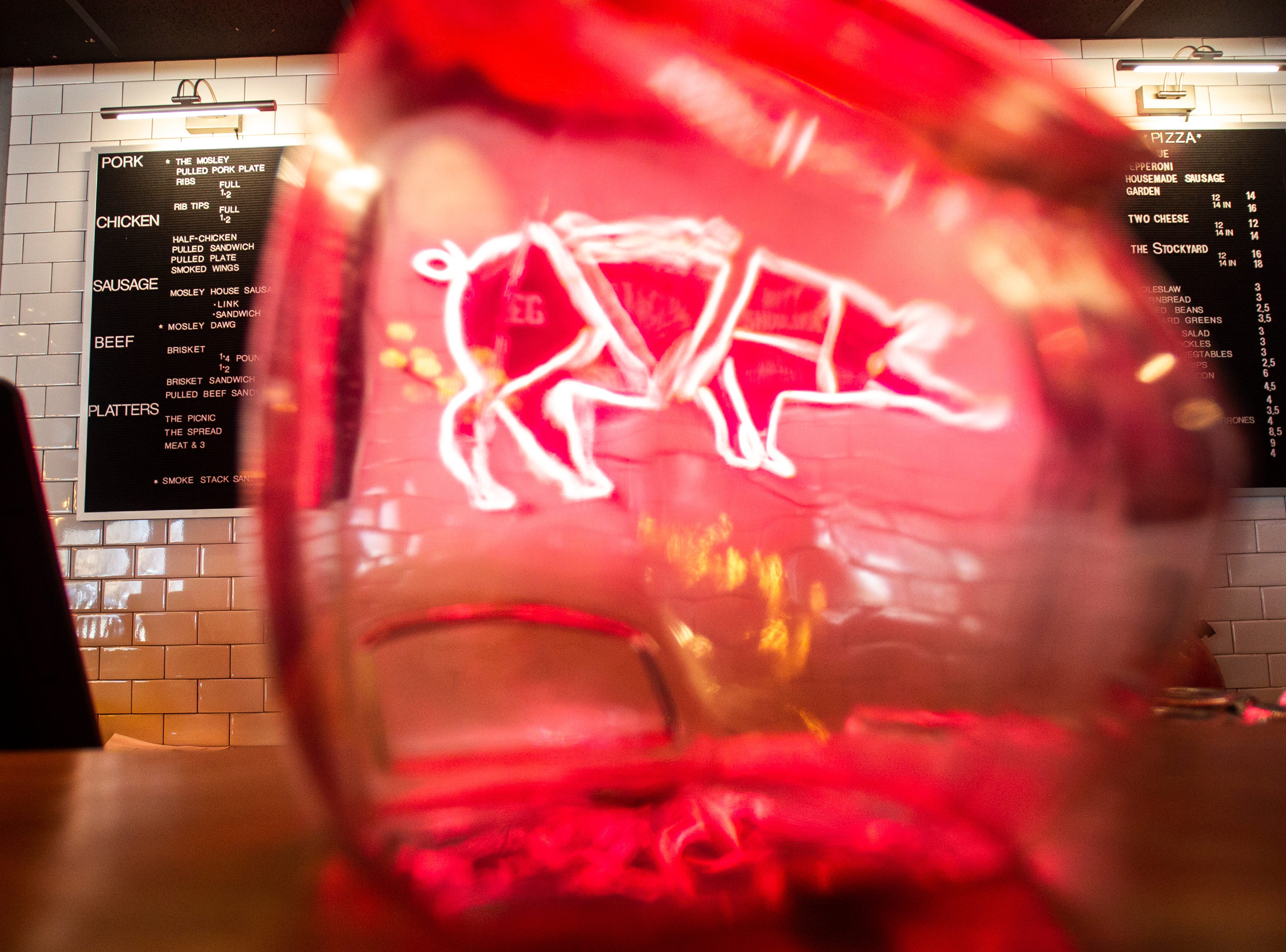 A neon sign in the shape of a pig is seen through a tip jar at the counter on Wednesday, Nov. 21, 2018, at Mosley's Barbecue and Provisions in North Liberty.