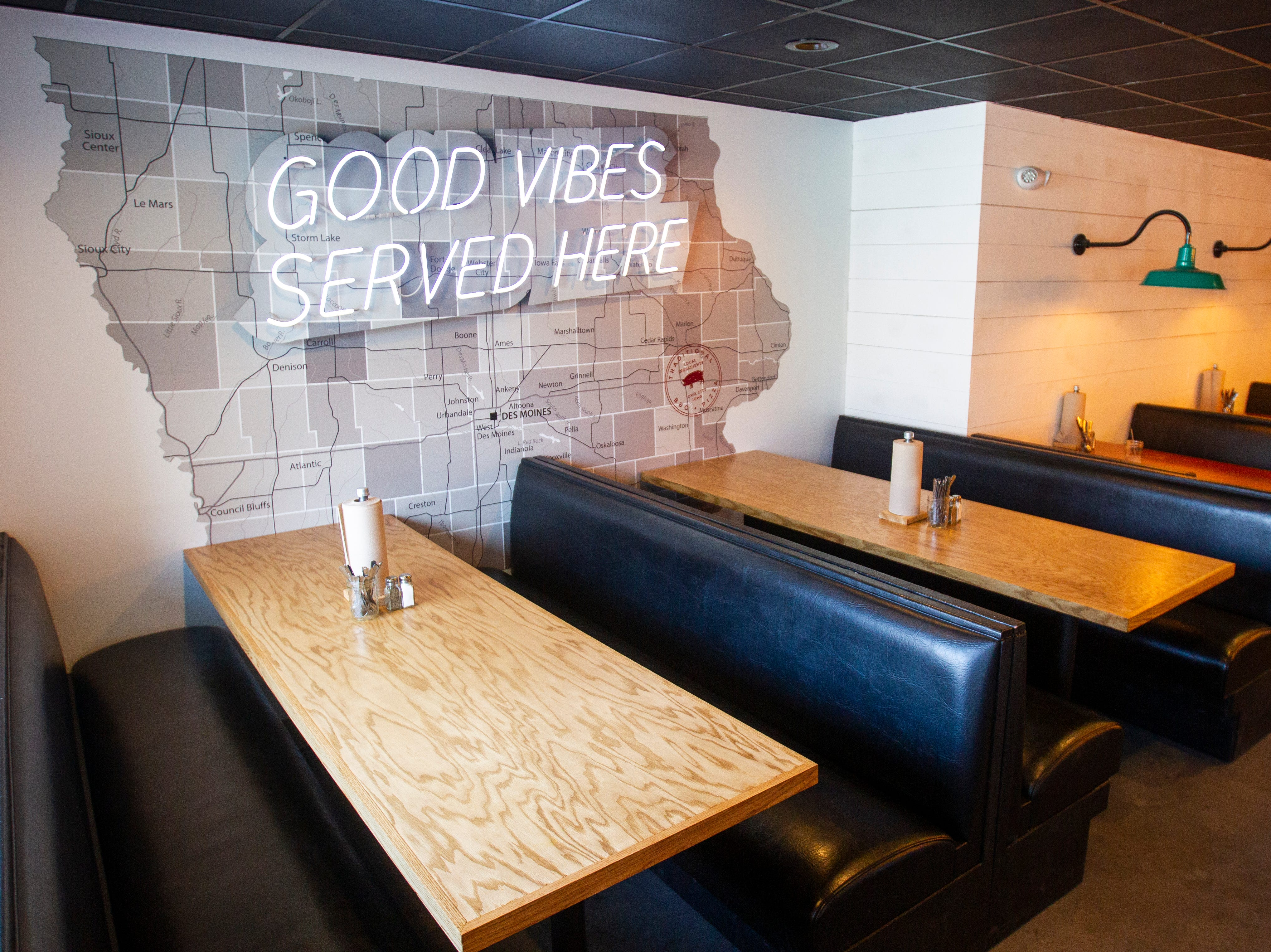 "A sign reads ""Good vibes served here,"" over a map of Iowa on the wall behind booths on Wednesday, Nov. 21, 2018, at Mosley's Barbecue and Provisions in North Liberty."