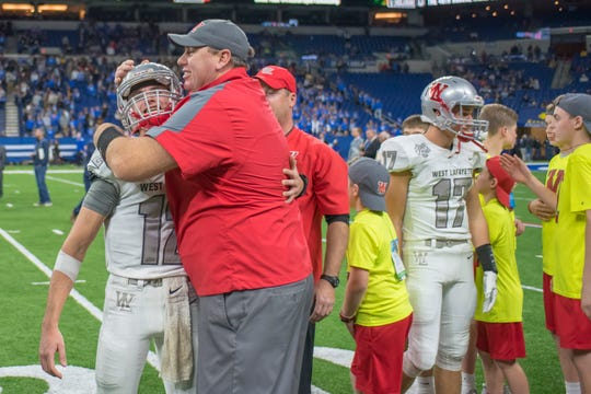 West Lafayette assistant coach Kelly Kitchel congratulates quarterback Kyle Adams after the Red Devils won the Class 3A state championship last November.