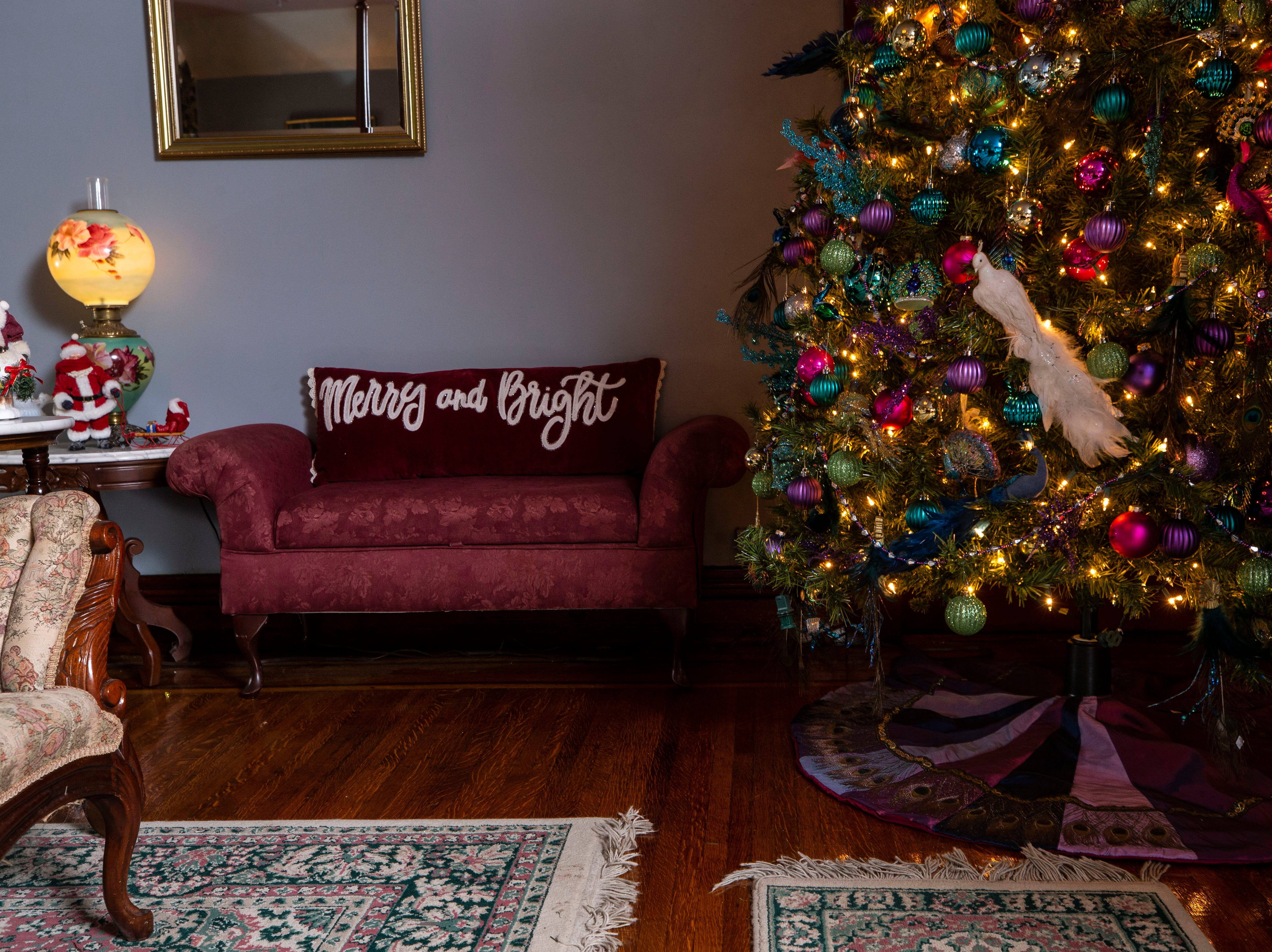 A Christmas tree decorates a corner of a third-floor bedroom as a holiday pillow decorates a sitting couch.